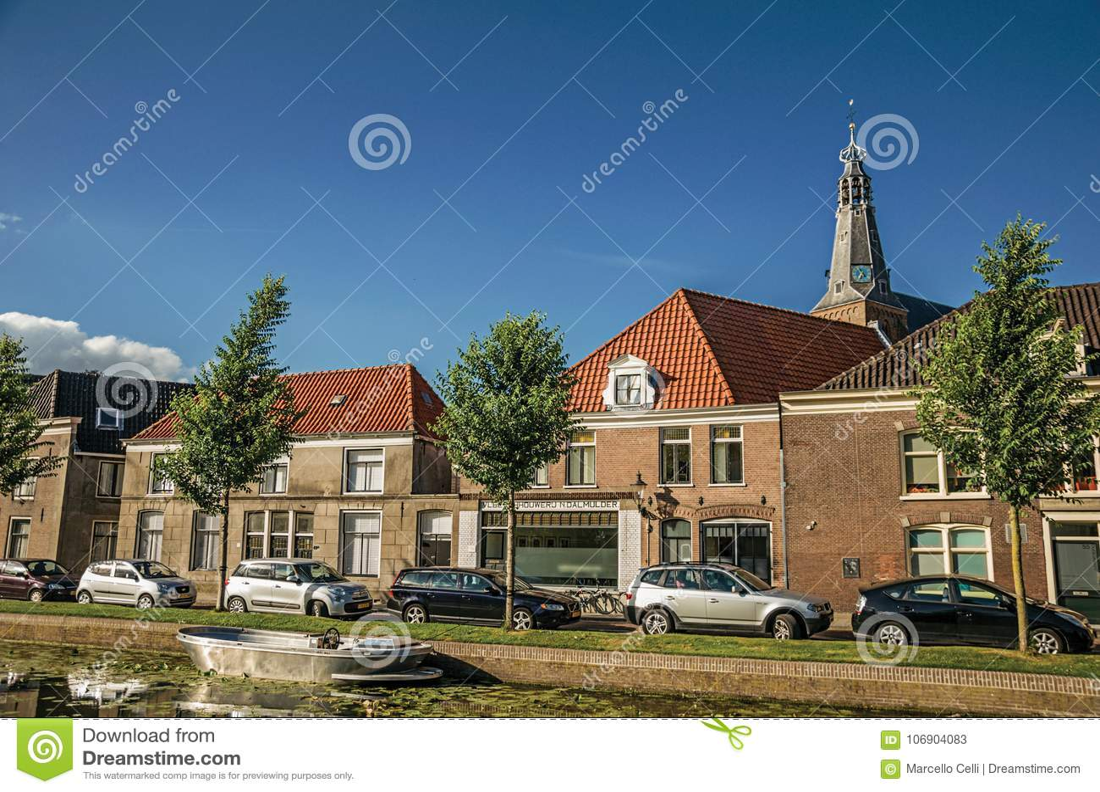 Wykładający kanał z łodzią, kościelny dzwonkowy wierza i domami na zmierzchu w Weesp,