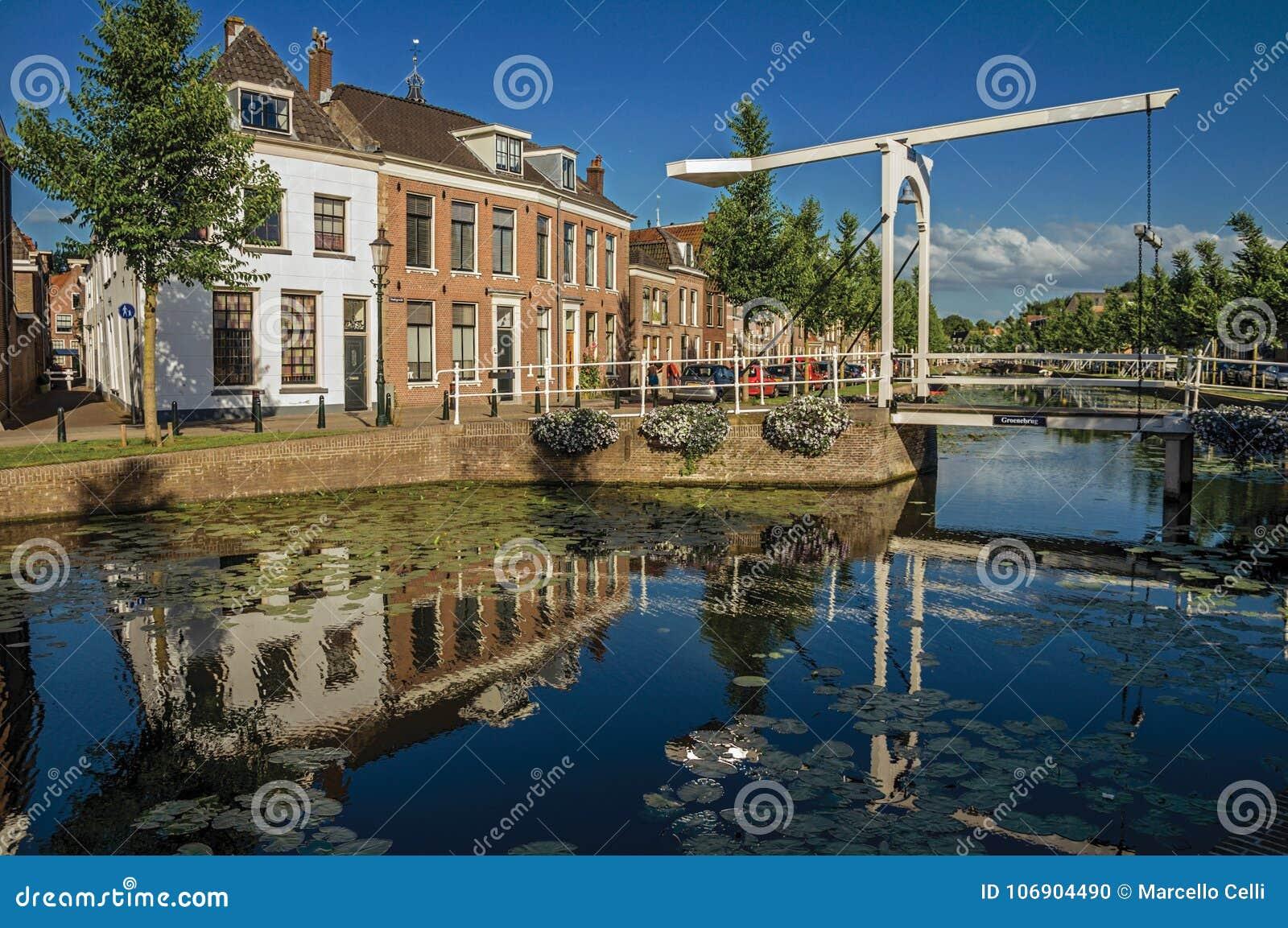 Wykładający kanał z nadwodnymi roślinami, bascule mostem i cegła domami przy bankiem na zmierzchu w Weesp,
