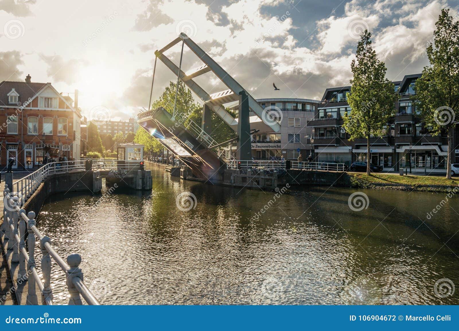 Wykładający szeroki kanał z domami i podnoszący bascule most na zmierzchu w Weesp