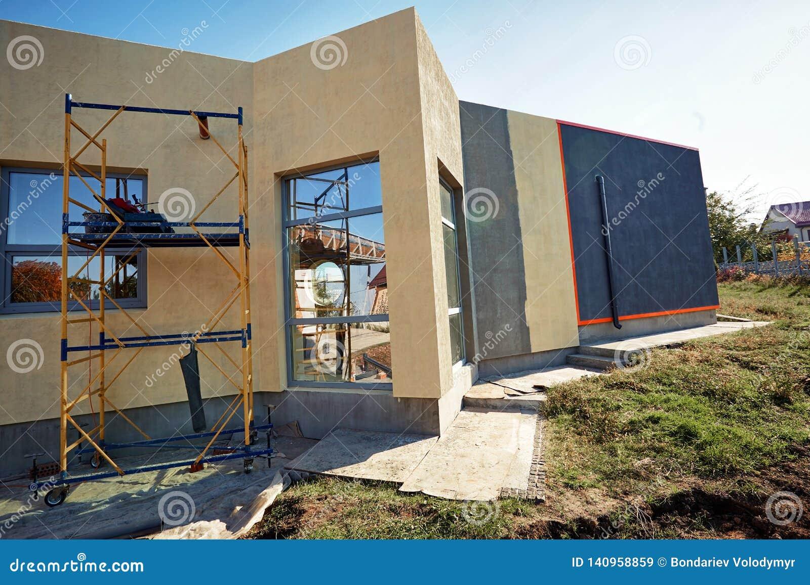 Wykończeniowy budować na fasadzie budynek z używa narzędzia dla kończyć