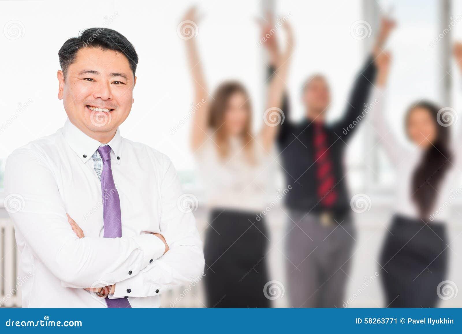 Wykonawczy azjatykci szef z jego pomyślną biznes drużyną przy tłem