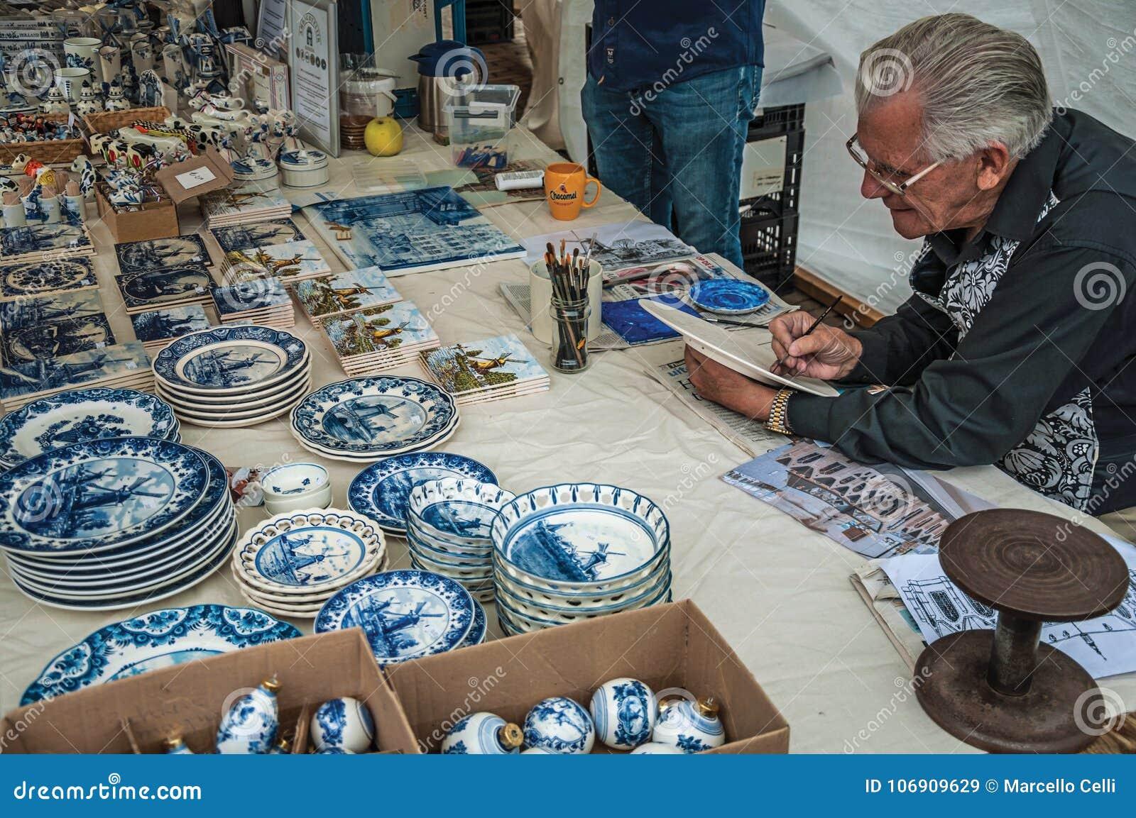 Wykwalifikowany rzemieślnika obrazu crockery w regionu typowym stylu przy Gouda