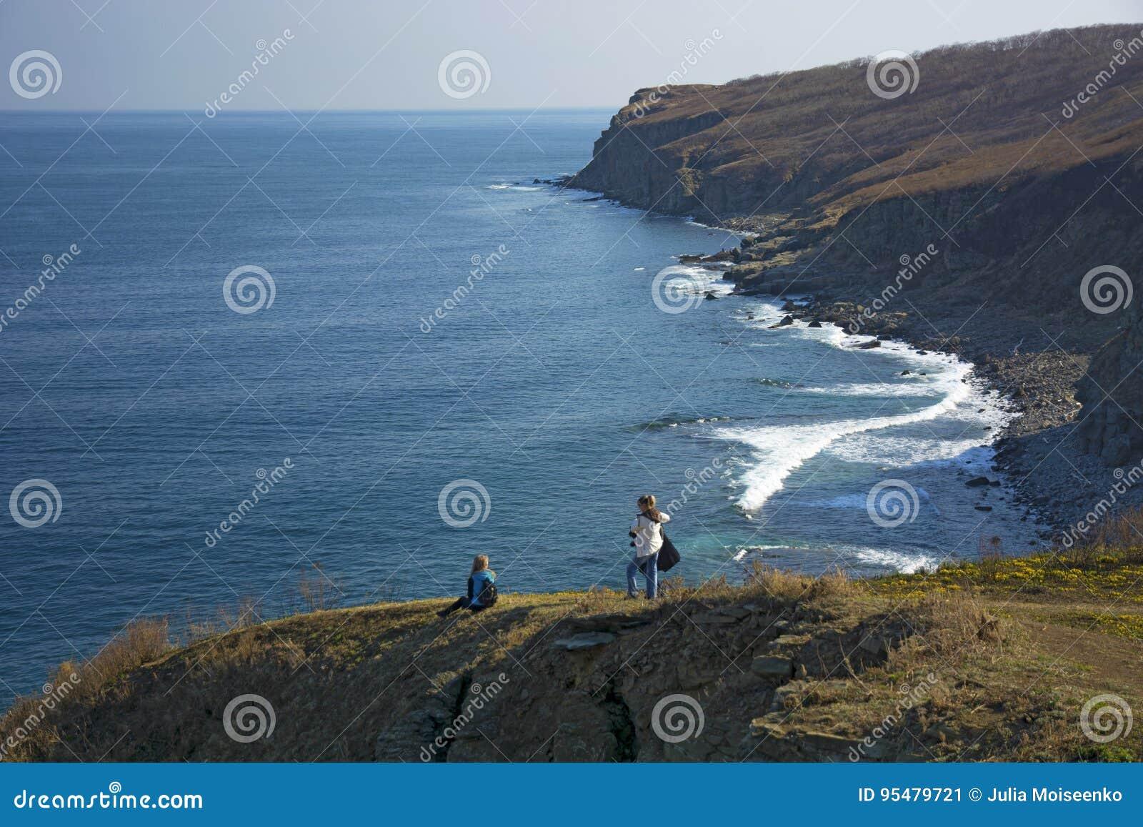 Wysoka faleza nad morze faleza pochodzi w morze, dużo chełbotanie machają i kamienie