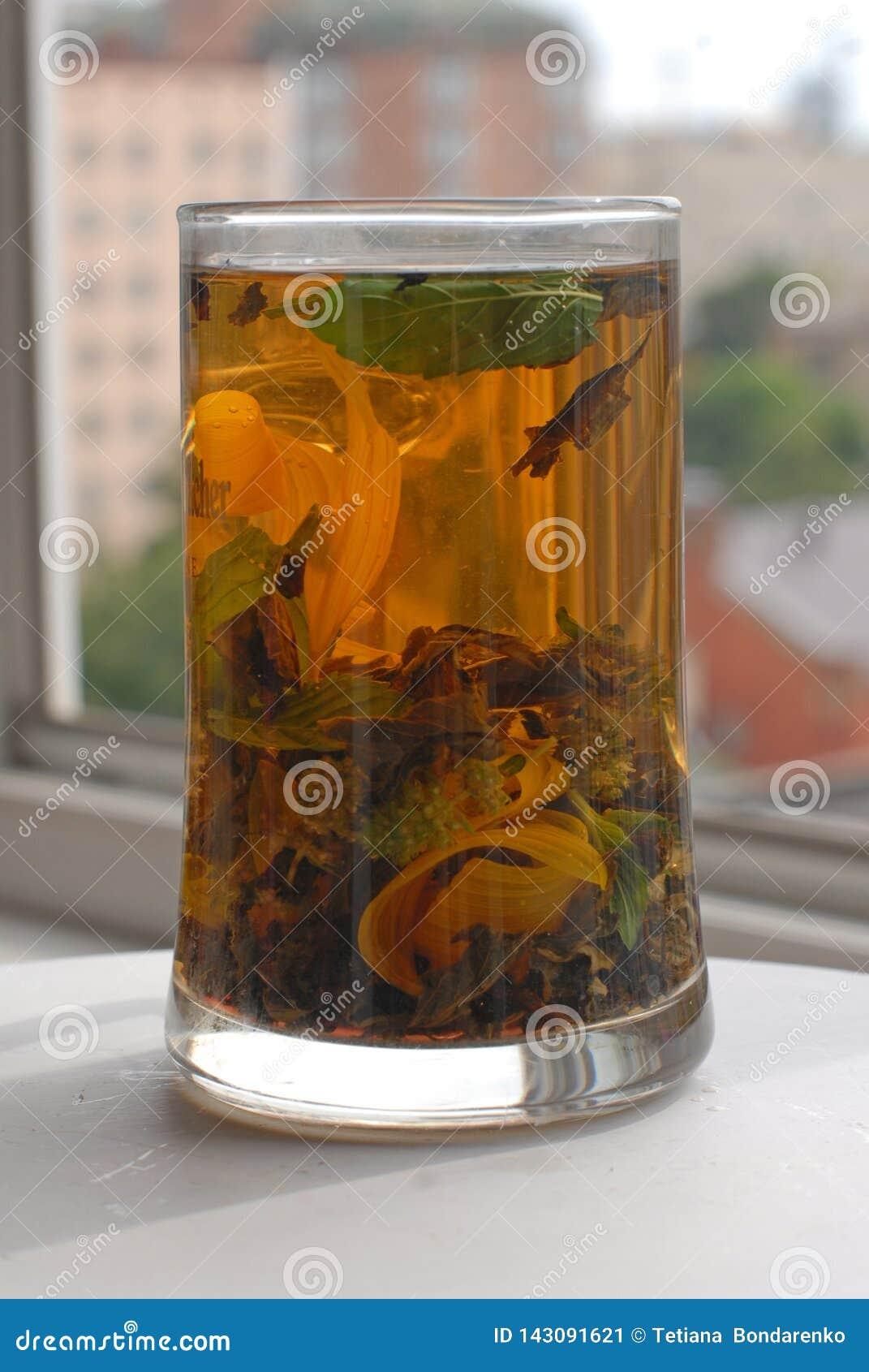 Wysoka szklana filiżanka z aromat ziołową herbatą