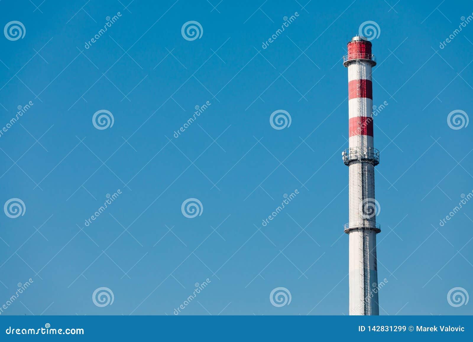 Wysoki fabryczny komin z trzy czerwonymi przerwami na th e wierzchołku nie dymiący