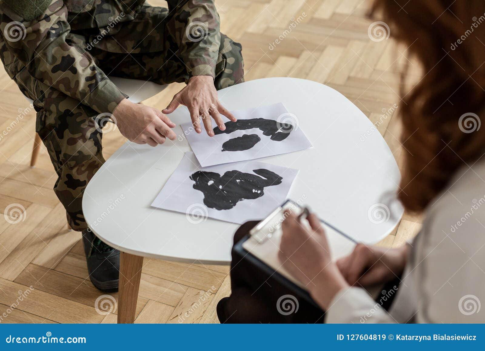 Wysoki kąt na żołnierzu w zieleń mundurze z plakatami podczas terapii z psychiatra