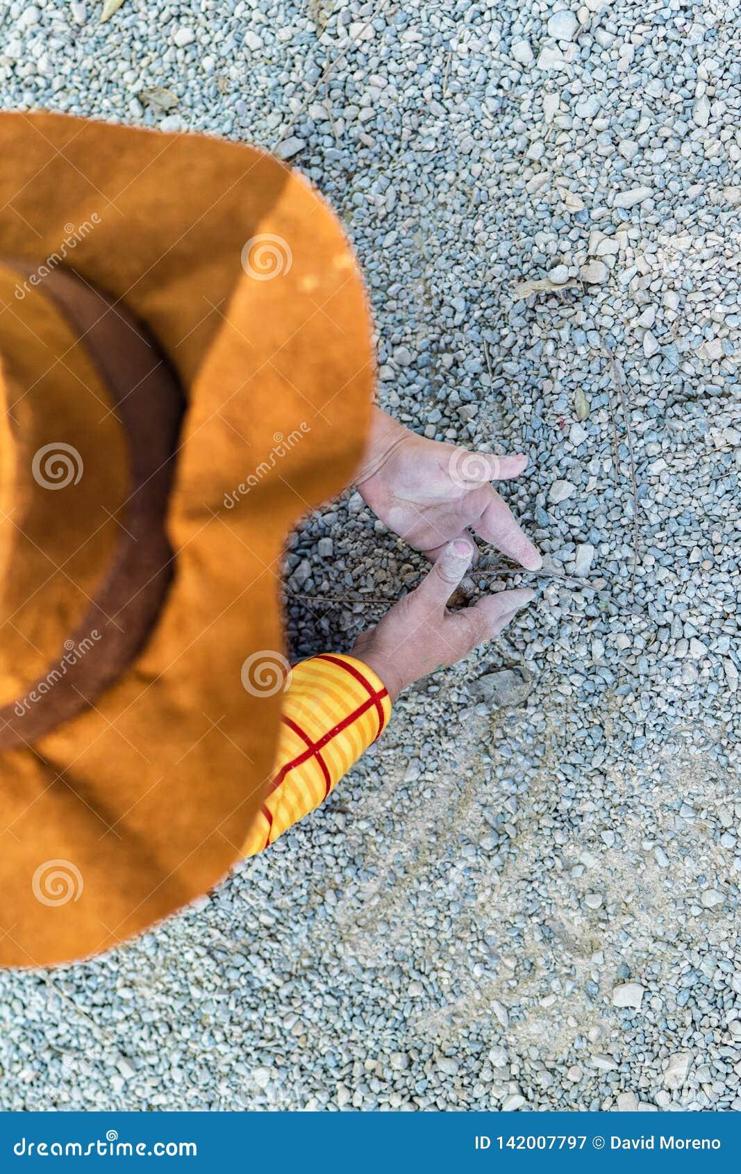Wysokiego kąta widok bawić się na ziemi z piaskiem i brudem kowbojska chłopiec