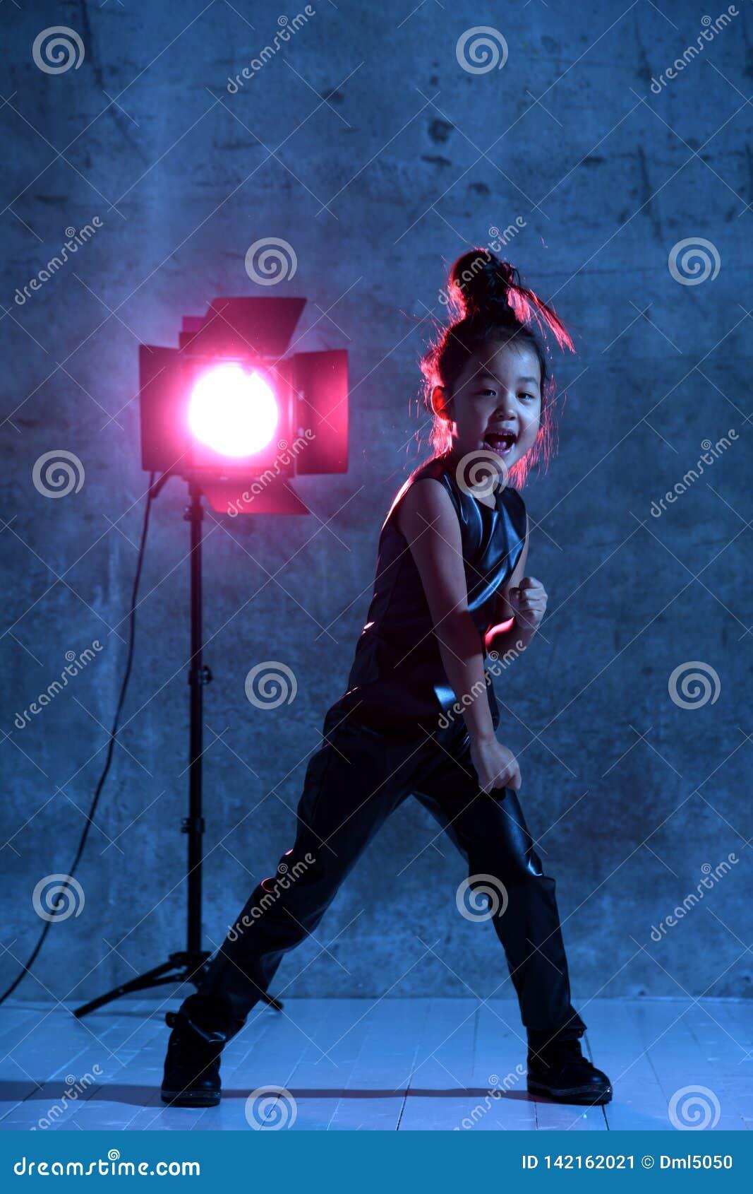 Wysokiej mody azjaty modela dziewczyna z pracownianym światło reflektorów kolorowym uzupełnia Uderza pięścią i Wrzeszczy