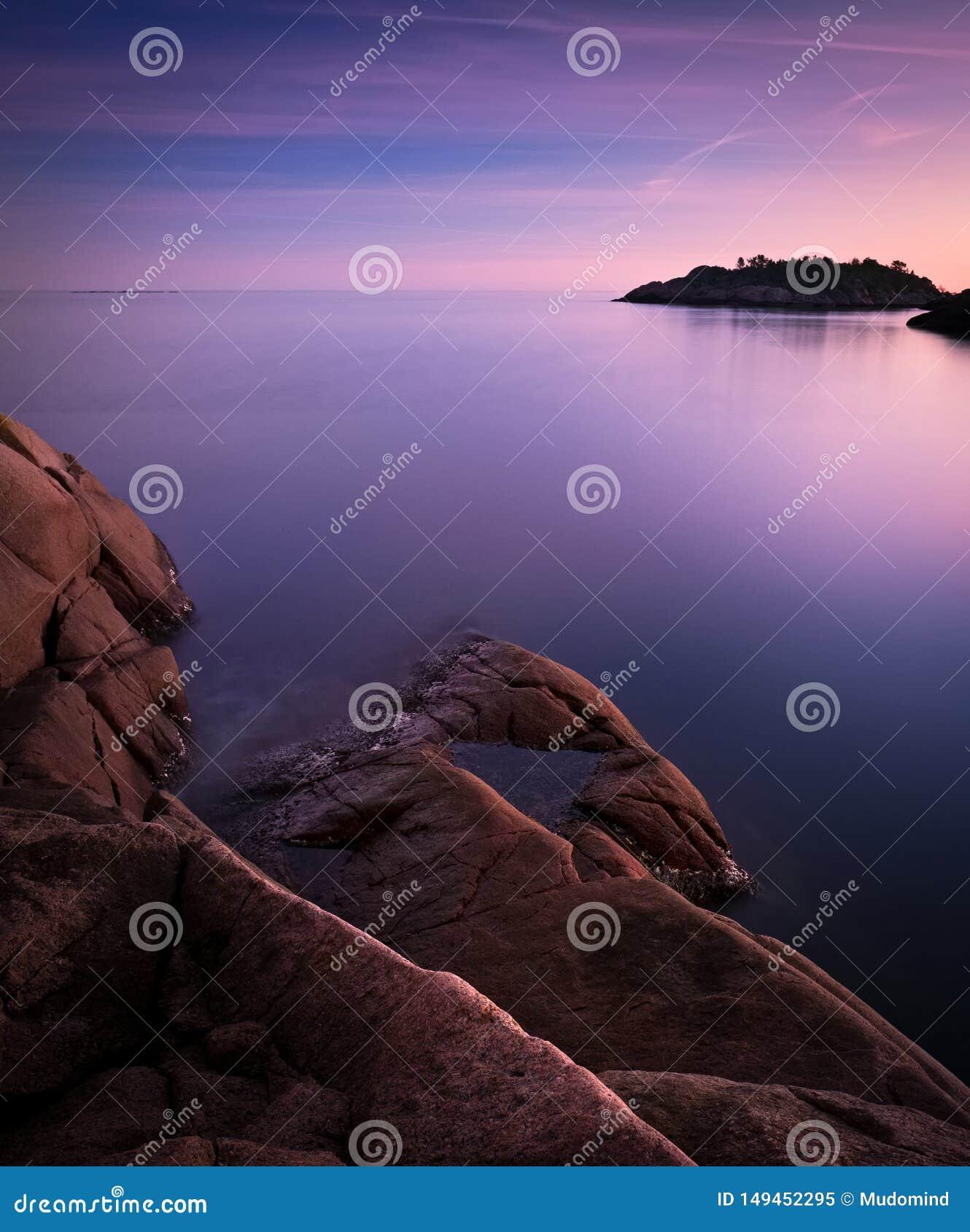 Wyspa i ska?a w milky purpurowym morzu