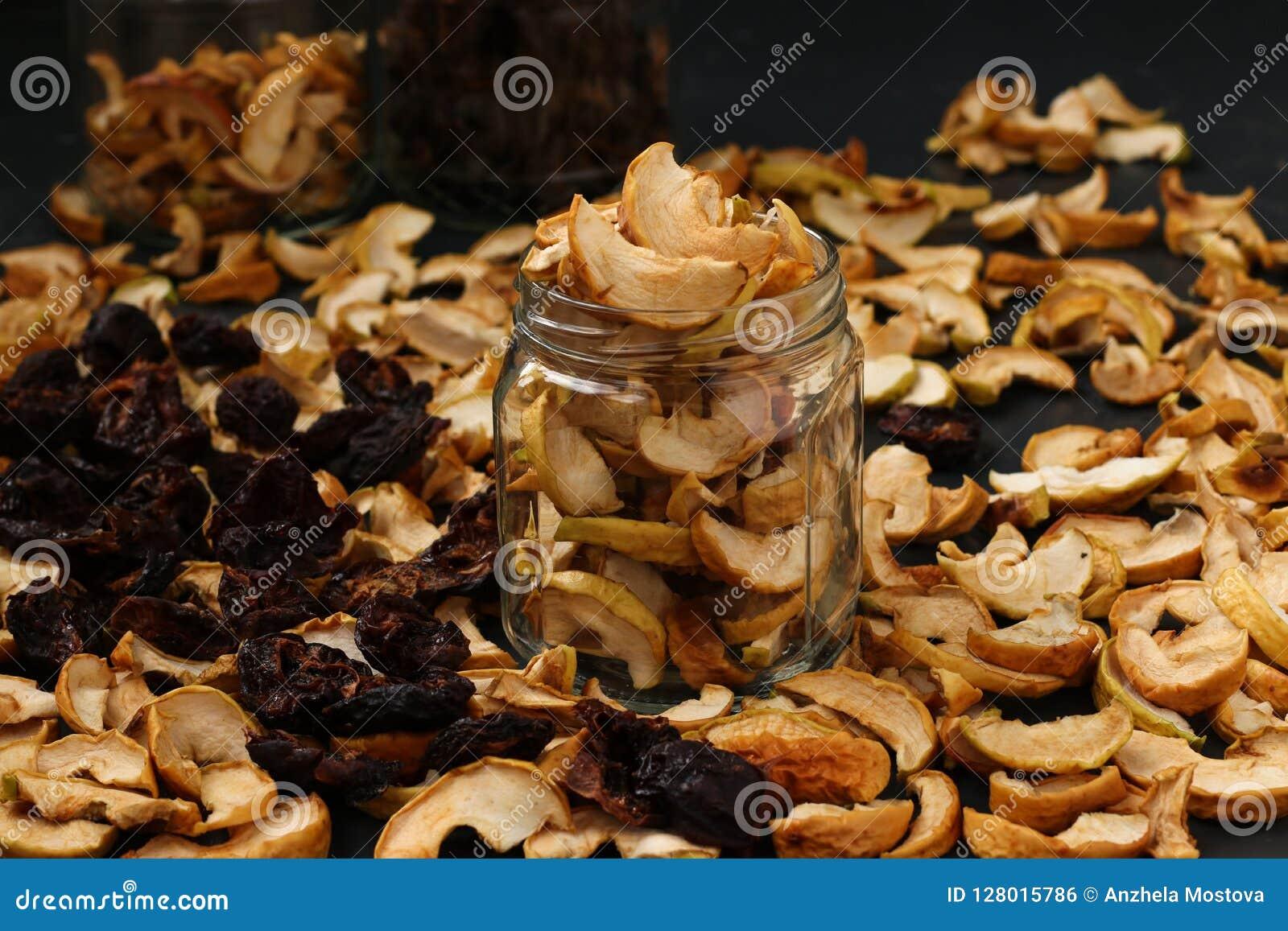 Wysuszone owoc w szklanych słojach na ciemnym tle