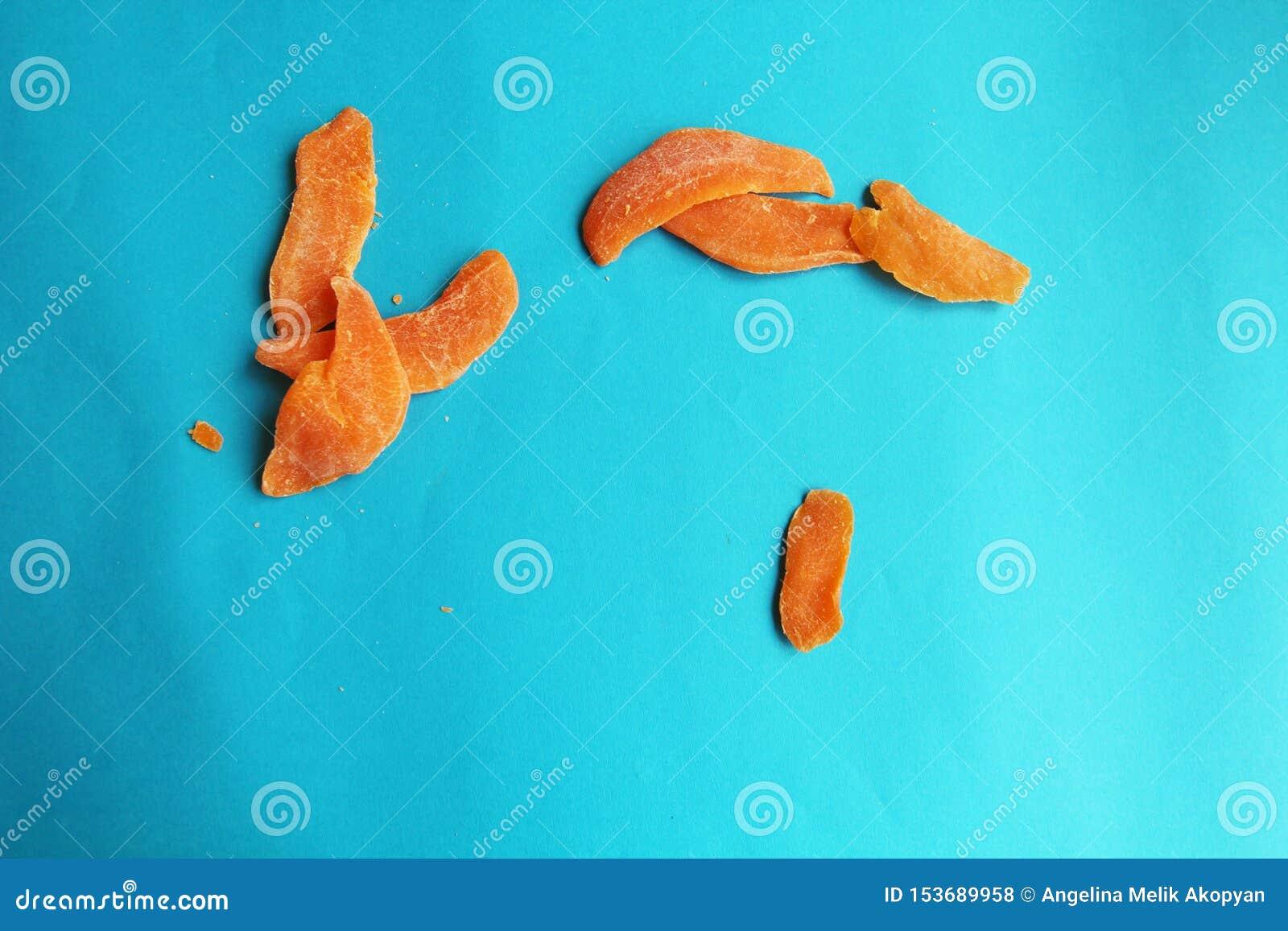 Wysuszonych owoc mangowy pomarańczowy plasterek na błękitnym jaskrawym tle Smakowity yummy dieting