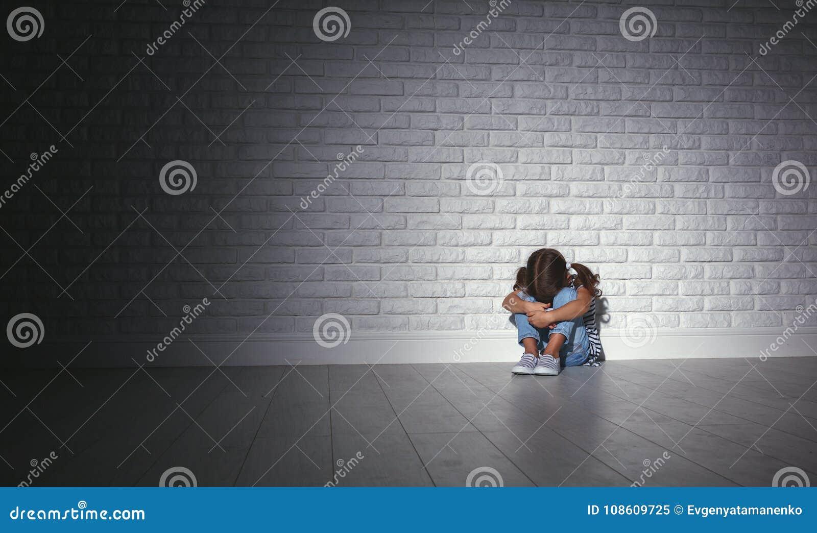 Wzburzona smutna smutna dziecko dziewczyna w stresie płacze przy pustą zmrok ścianą