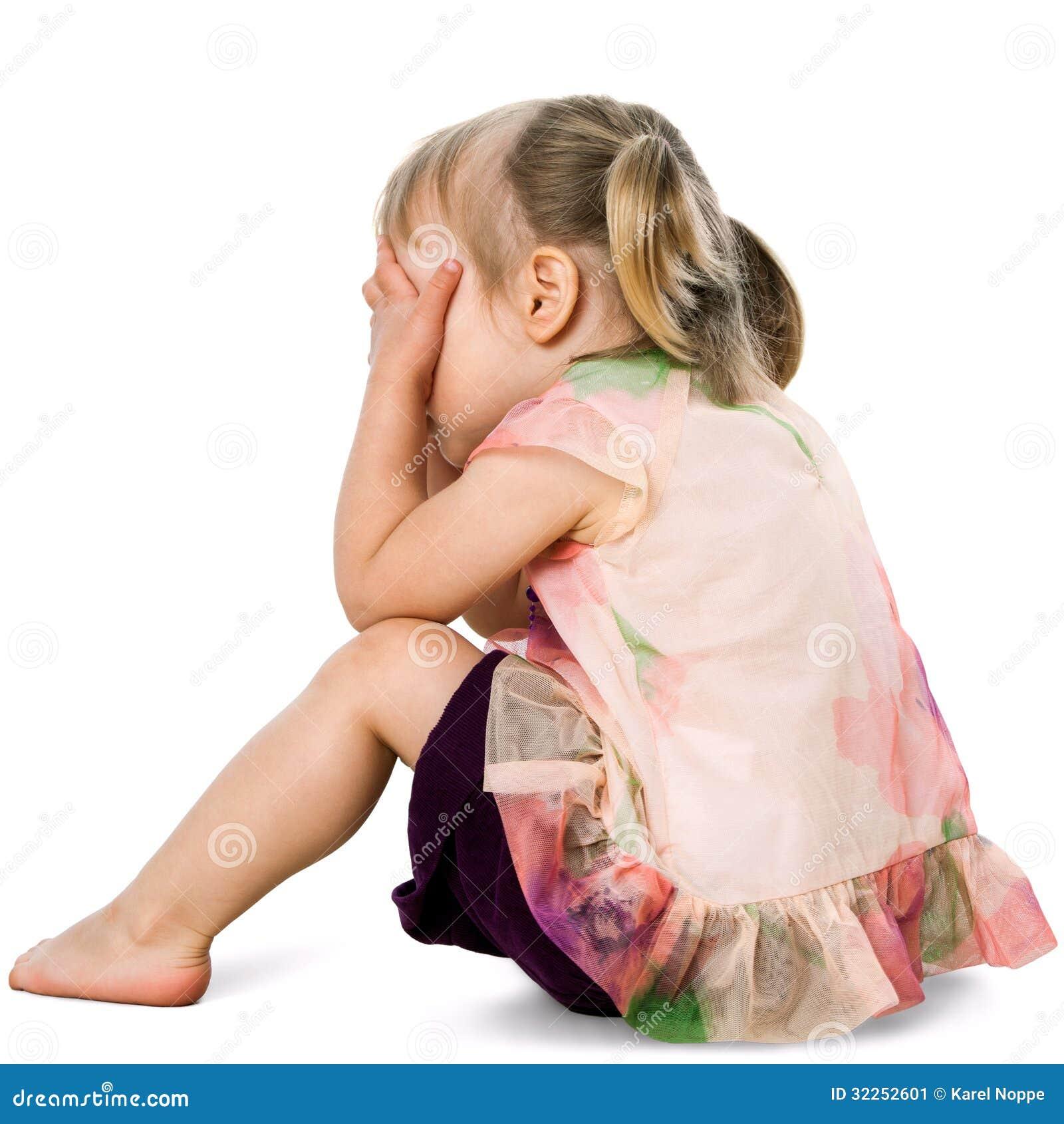 Wzburzony dzieciak chuje twarz z rękami.