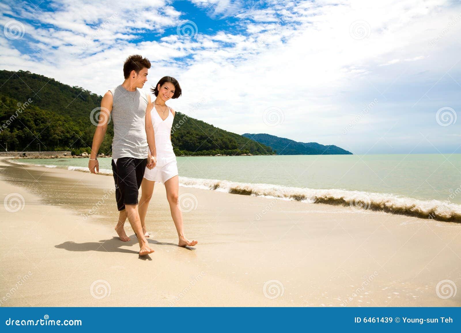 Wzdłuż plażowej kochających chodzących młodych par