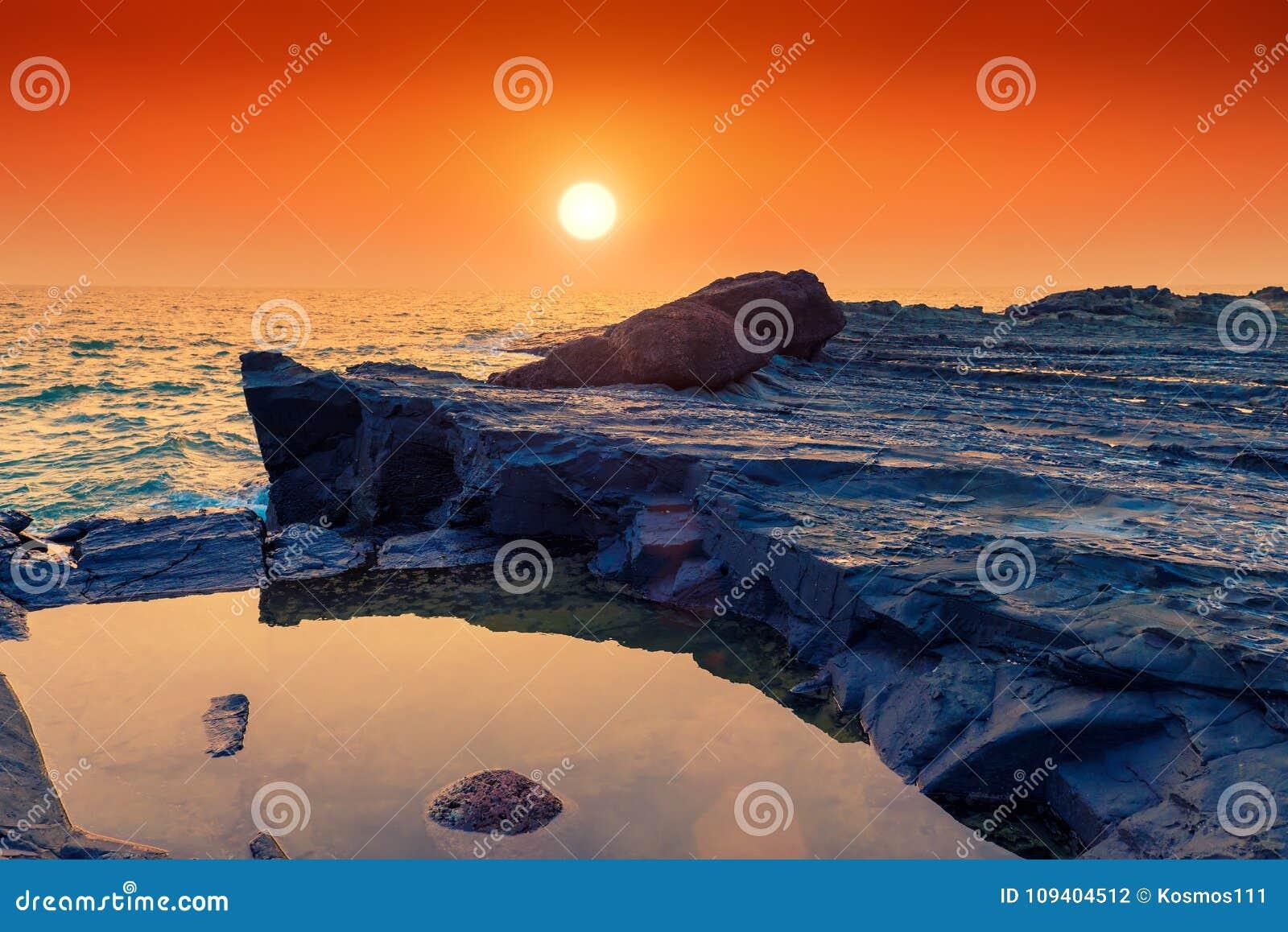 Wzmacniający ocean przy zmierzchem i lawa