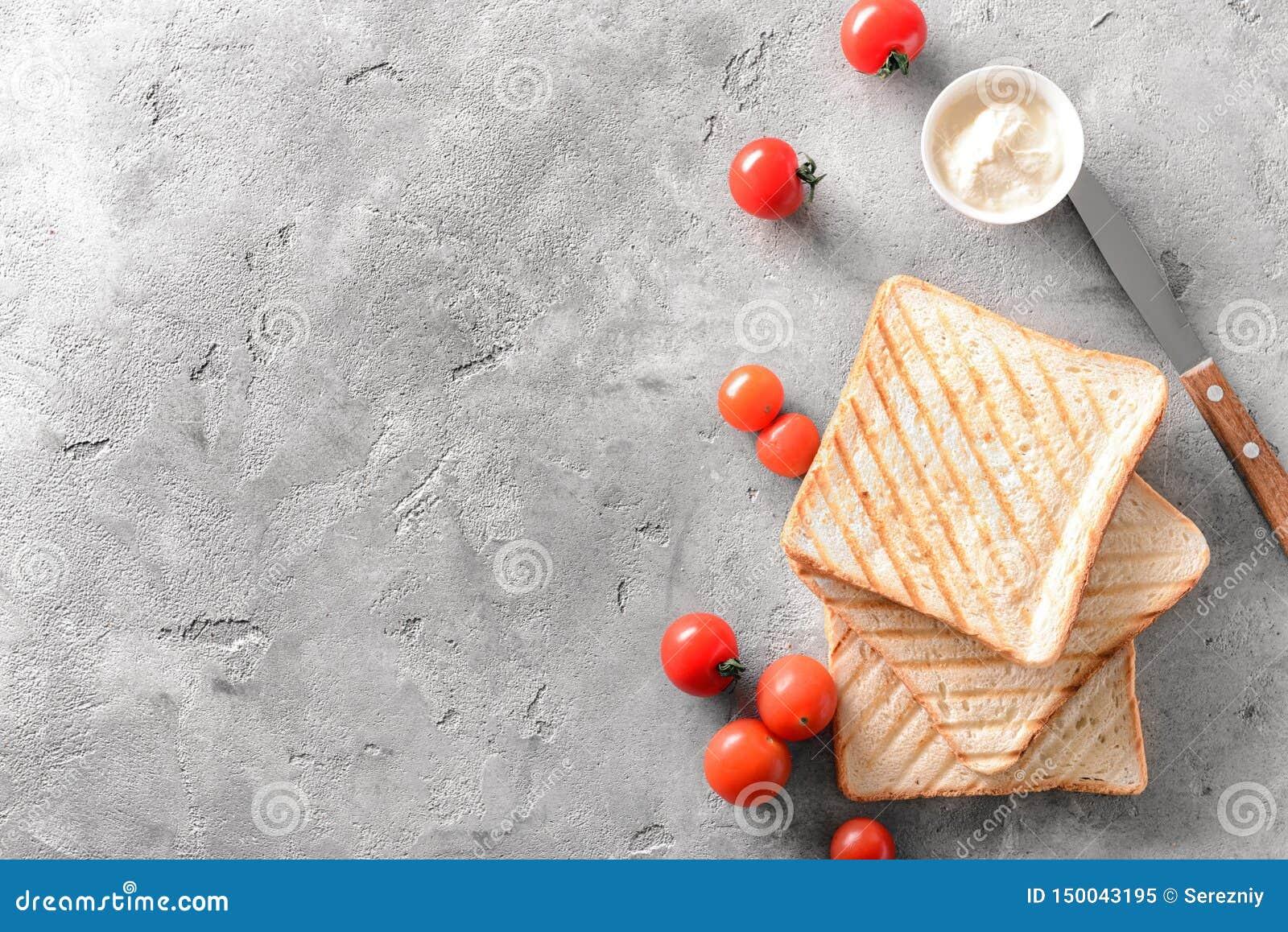 Wznoszący toast chleb, kremowy ser i czereśniowi pomidory na popielatym tle, odgórny widok
