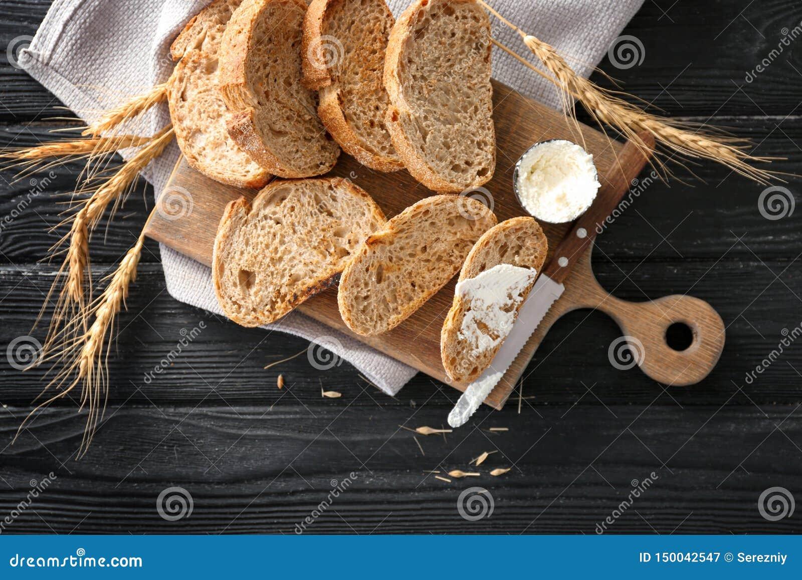 Wznoszący toast chleb z kremowym serem na drewnianej desce, odgórny widok