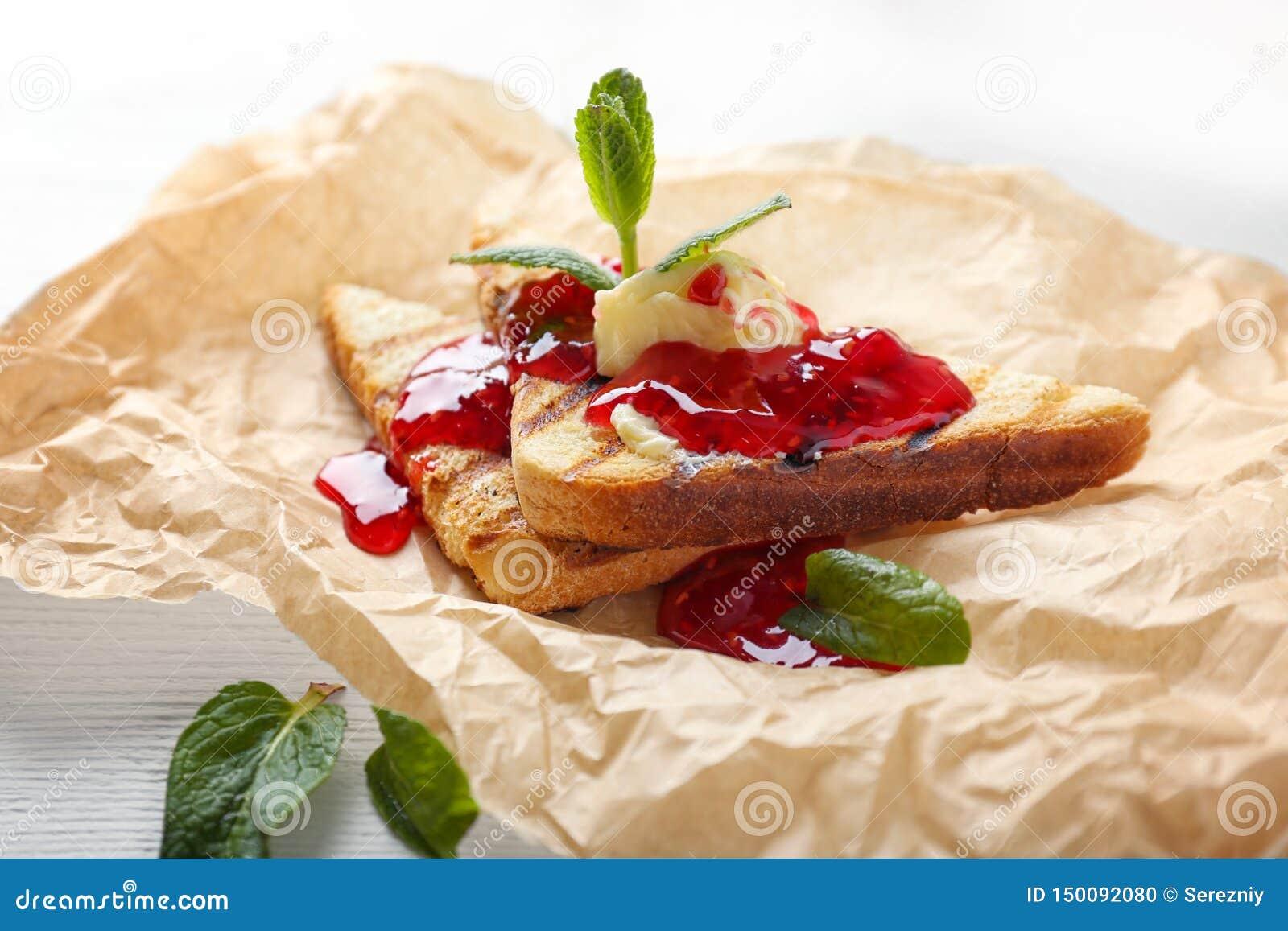 Wznoszący toast chleb z słodkim dżemem, masłem i mennicą na pergaminie,