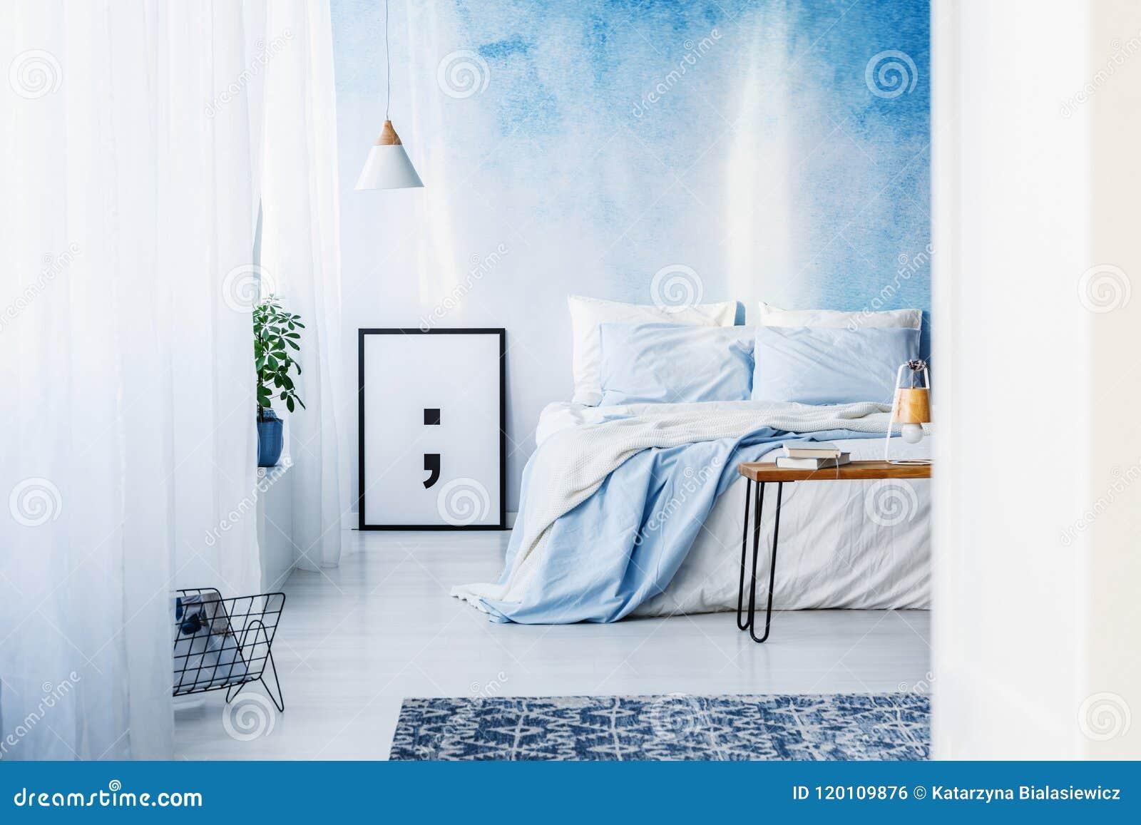 Wzorzysty dywanik i plakat w błękitnym sypialni wnętrzu z łóżkiem znowu