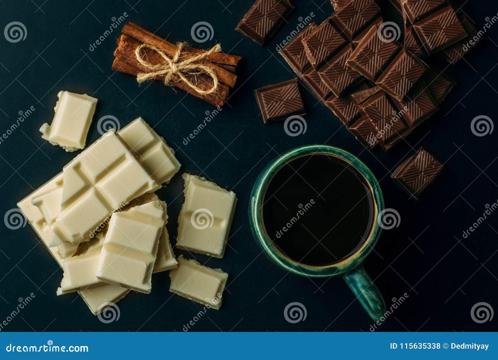 Xícara de café, barras de chocolate quebradas e pilha brancas e pretas de canela na tabela preta, vista superior