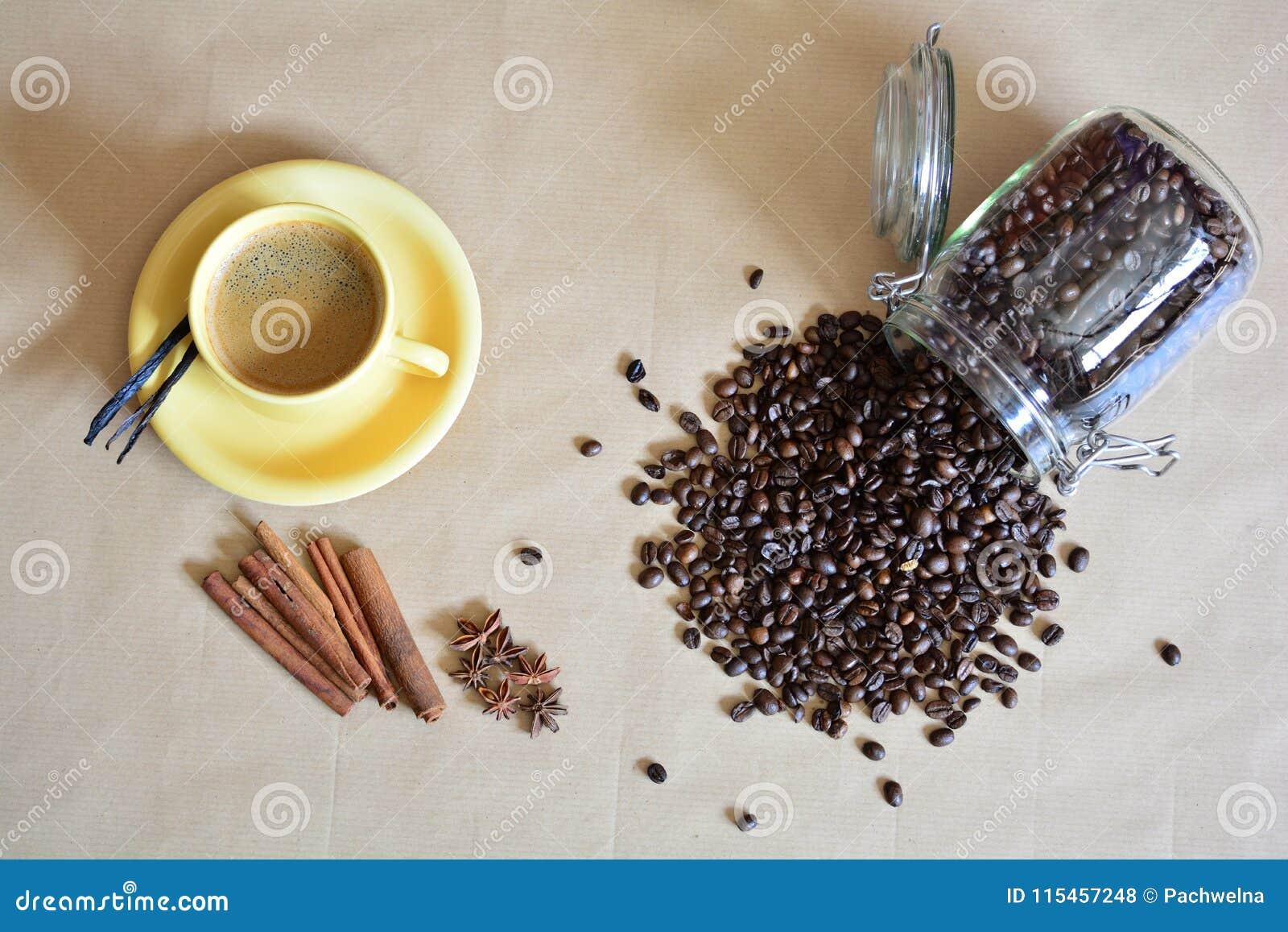 Xícara de café com as varas do anis, da baunilha e de canela mais alguns feijões de café derramados
