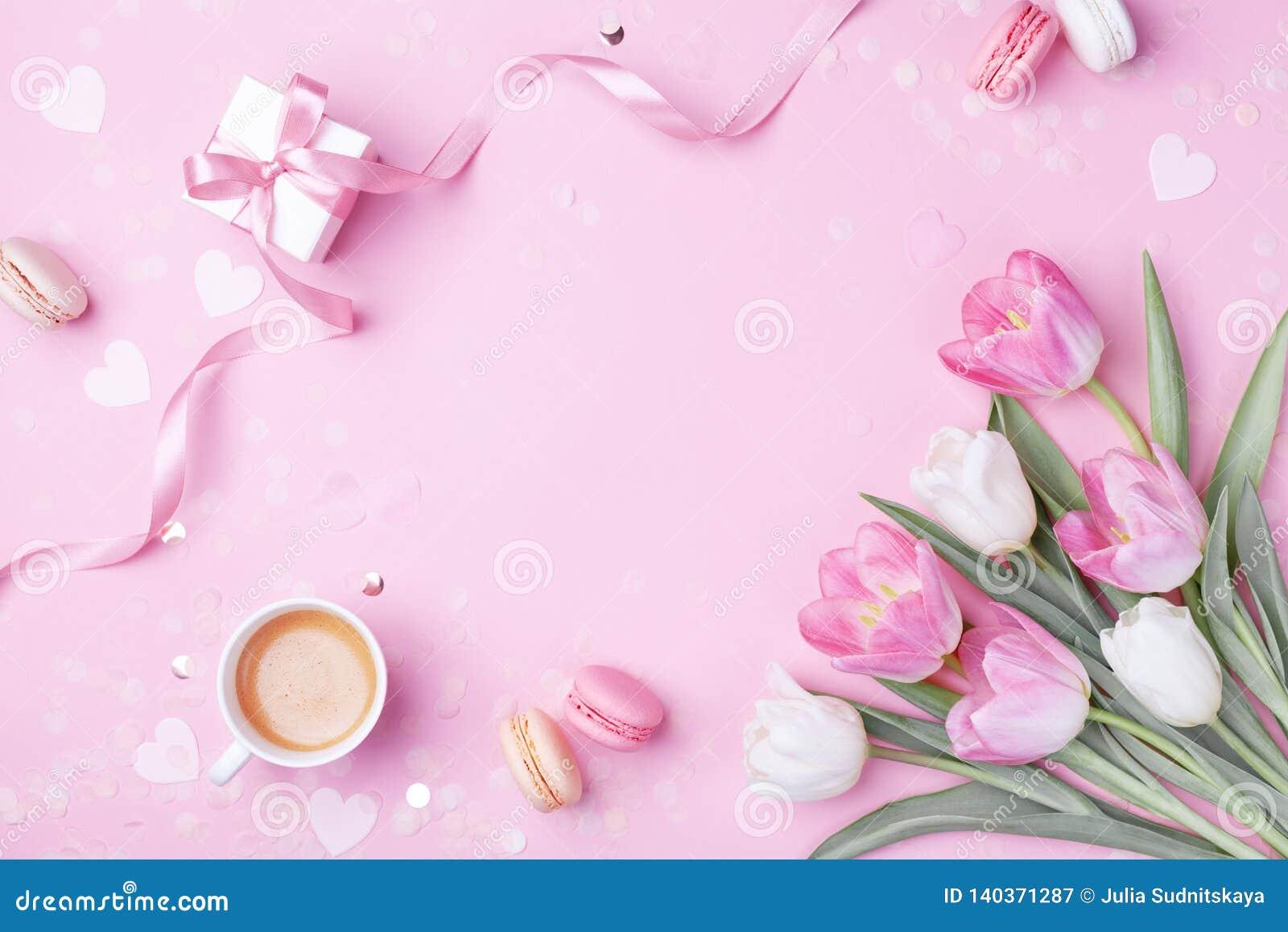Xícara de café da manhã, macaron do bolo, presente ou caixa e flores atuais da tulipa da mola no rosa Café da manhã para mulheres