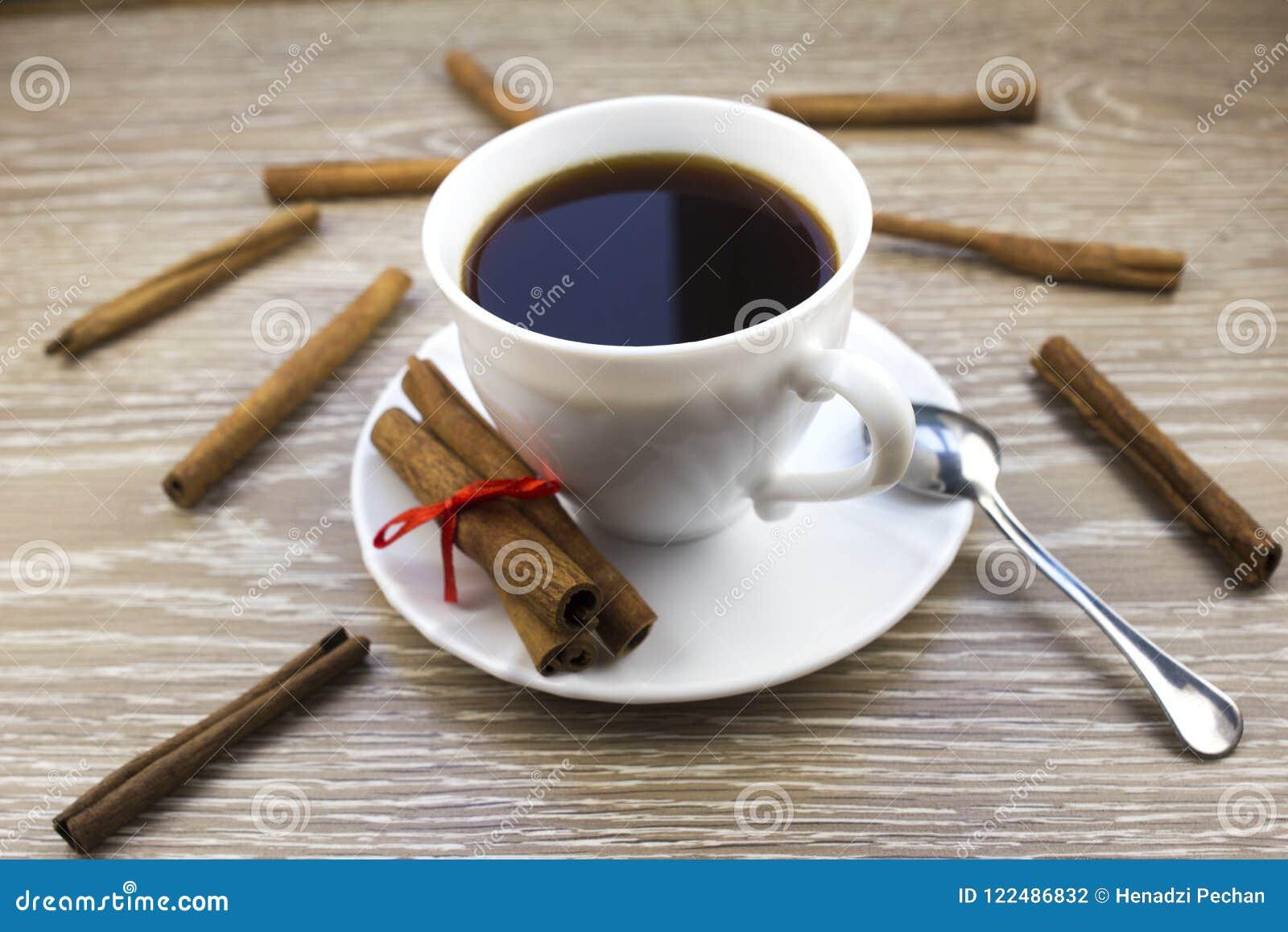 Xícara de café e canela brancas em um café de madeira do fundo