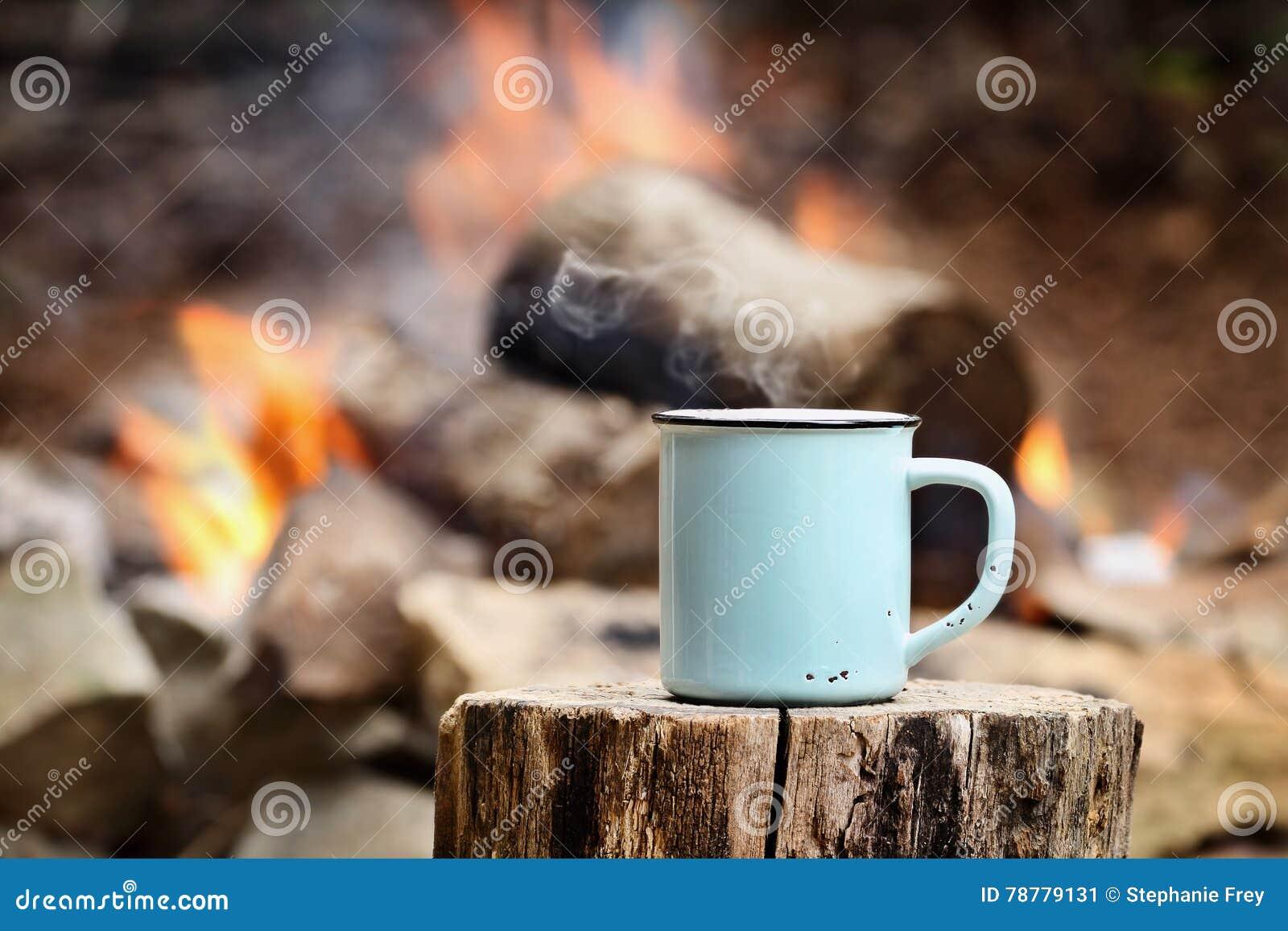 Xícara de café por uma fogueira