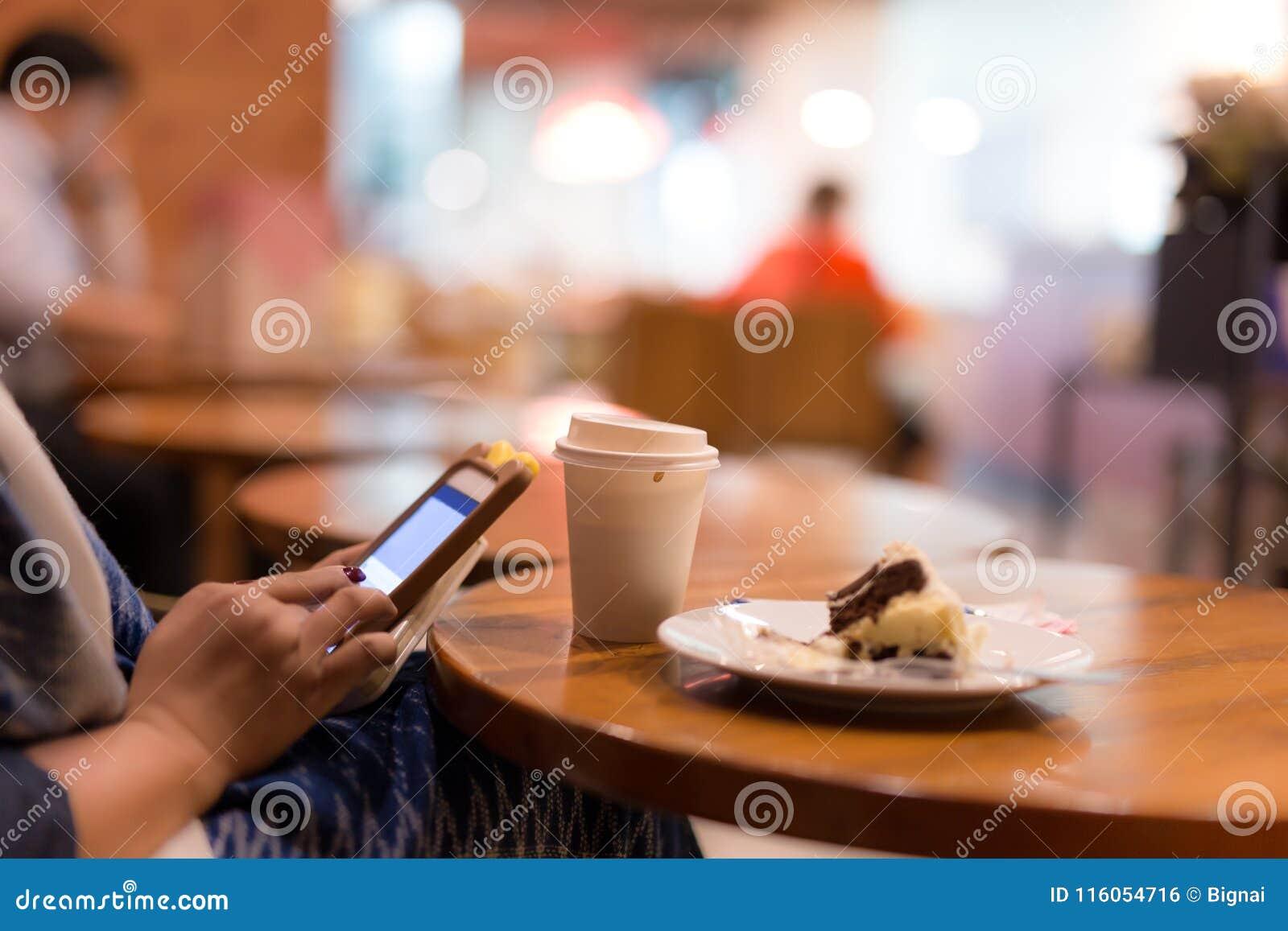 Xícara de café selecionada do foco com a mulher que usa a pedra de afiar e o eati da pilha