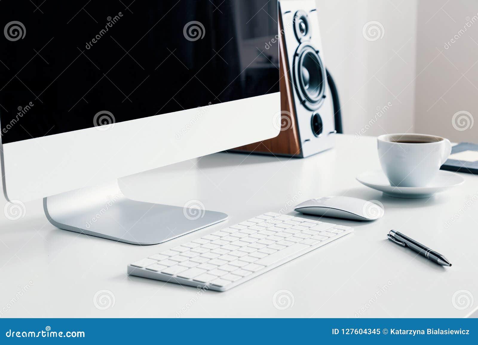 Xícara de café, teclado e computador de secretária na mesa no interior branco do escritório domiciliário Foto real