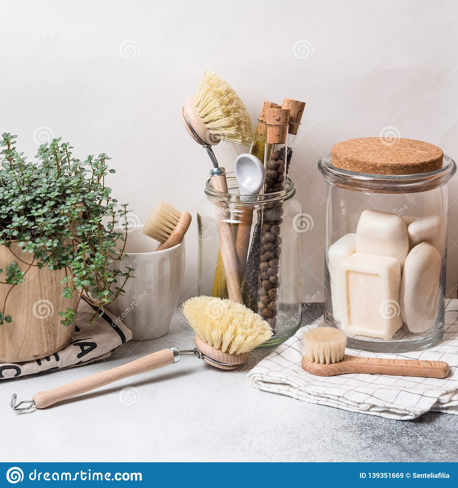 Zero waste concept. Eco-friendly kitchen set. Brushes, soap in jar, spices in glass tubes and plant in wood flowerpot
