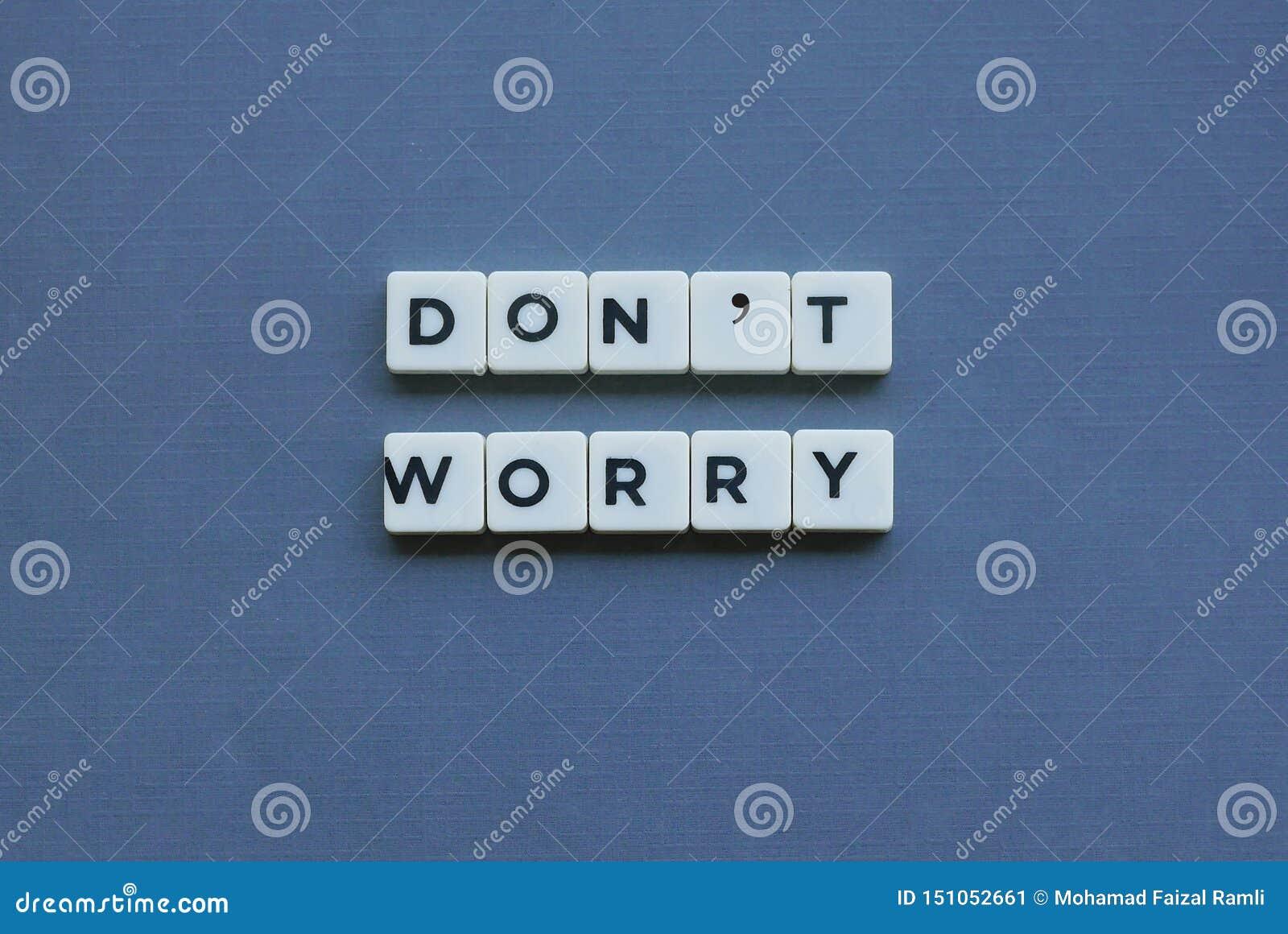 ' Don' t-Sorge ' Wort gemacht vom quadratischen Buchstabewort auf grauem Hintergrund