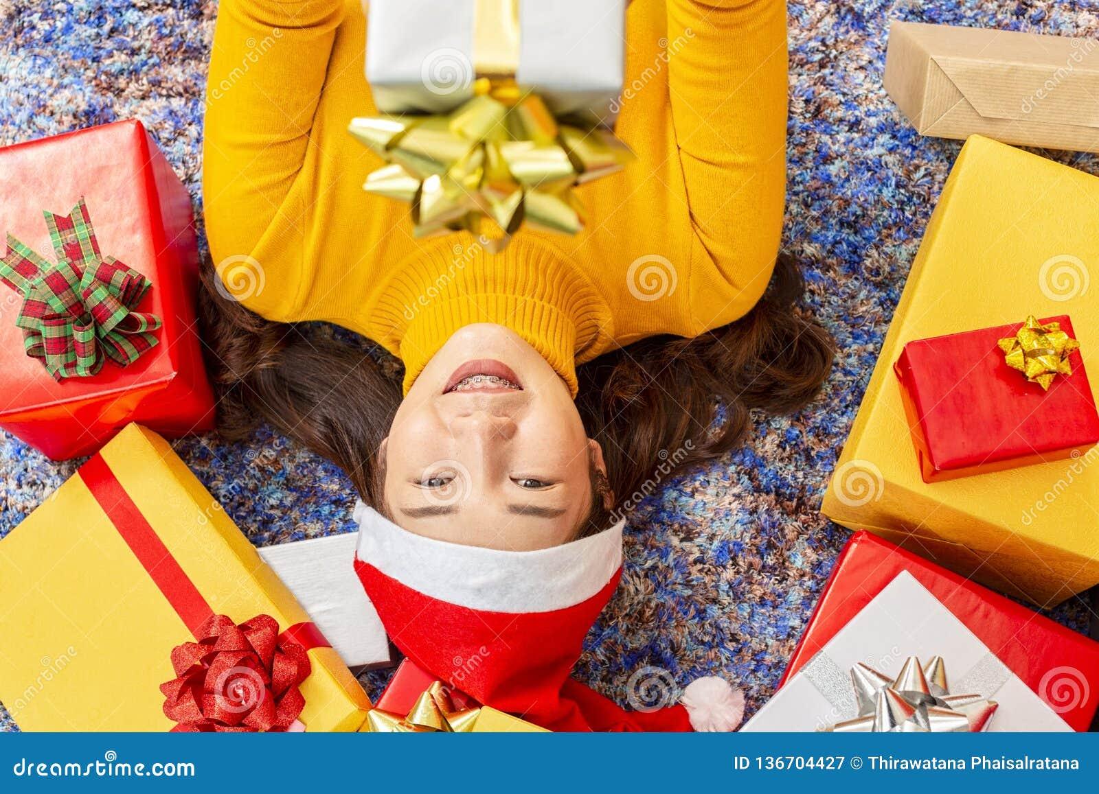 X-mas och feriebegrepp Lycklig kvinnlig med gåvaasken Unga kvinnor i röd gåva för jullockhänder som slås in med guld- papper och