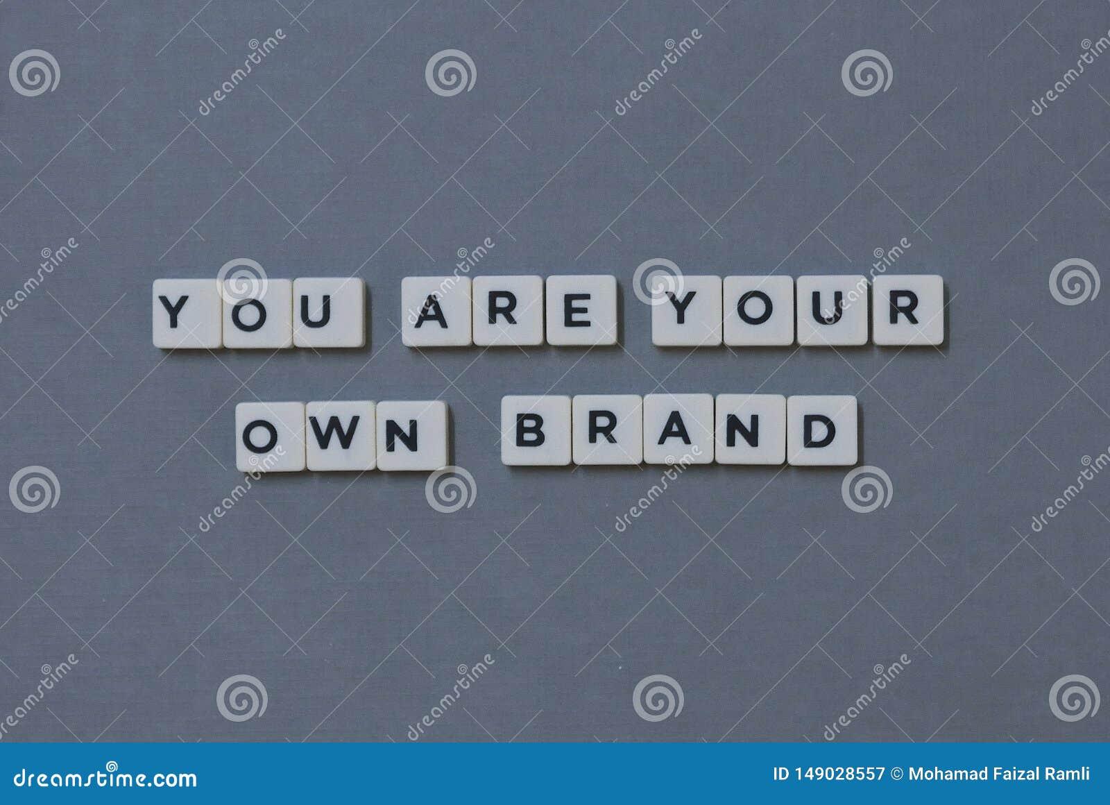 ' U bent Uw Eigen Merk ' woord van vierkant brievenwoord wordt gemaakt op grijze achtergrond die