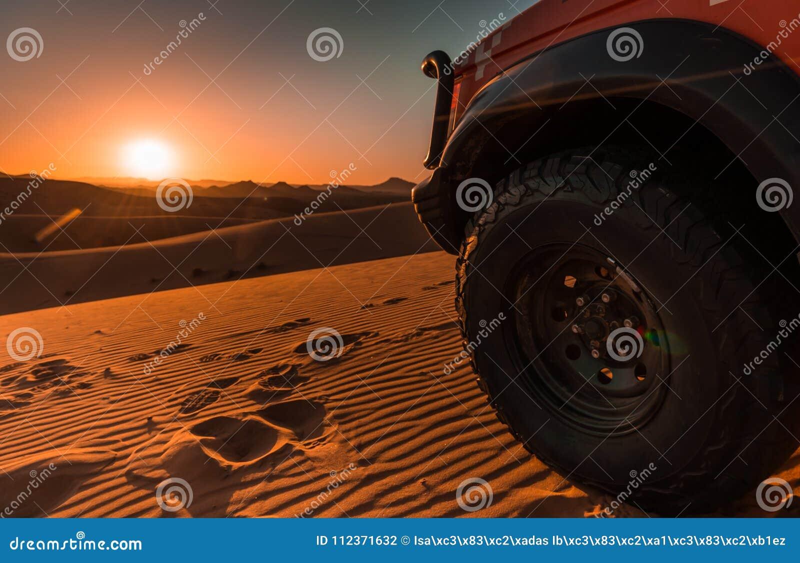 4x4 voertuig, woestijn en zonsondergang