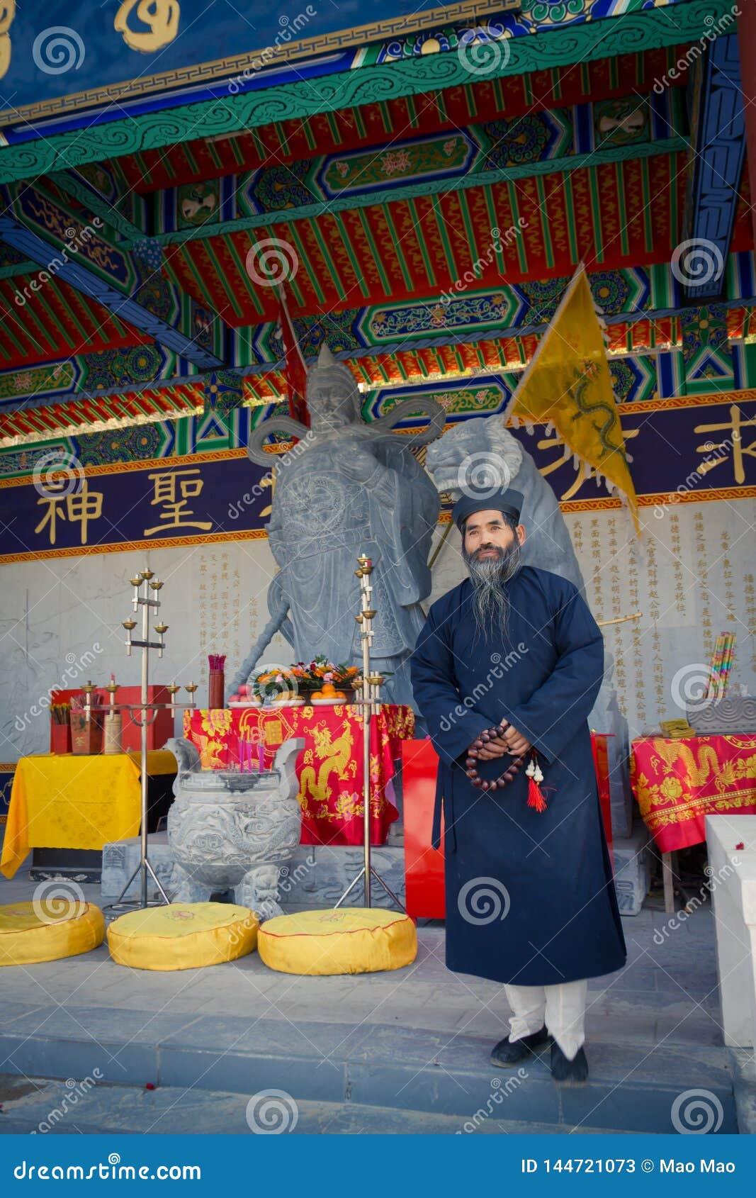XIAN, CHINA - 6 DE SETEMBRO DE 2013: O padre de meia idade da taoista veste um chapéu Manchurian macio, preto e um profundo-azul
