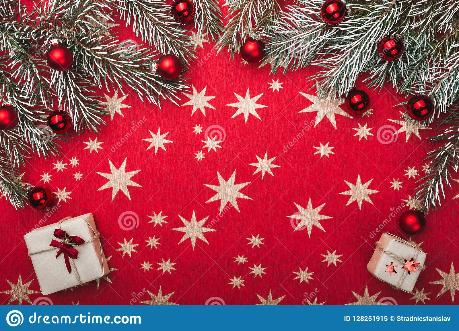 Xmas card, red background with stars. Space for your text. Fir branches with red balls. Top view