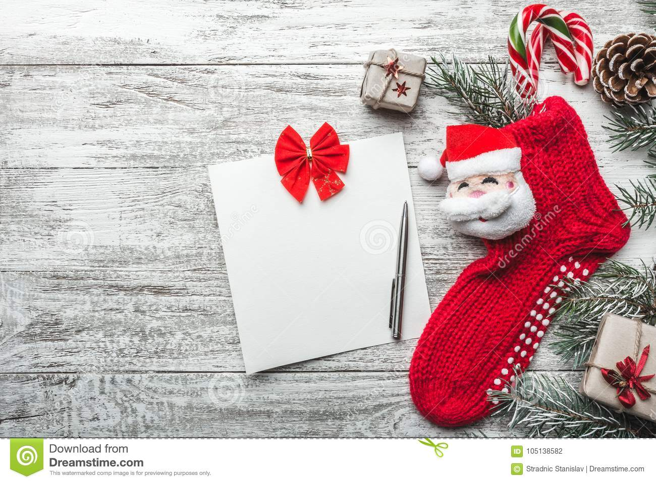wooden background painted white with a christmas sock and santa claus