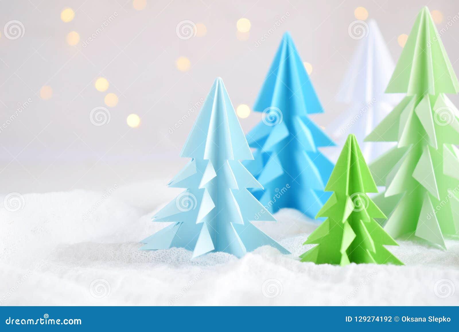 Xmas-träd för origami 3D från papper på vita bakgrunds- och bokehljus GLAD JUL OCH KORT FÖR NYTT ÅR pappers- konststil Kopierings