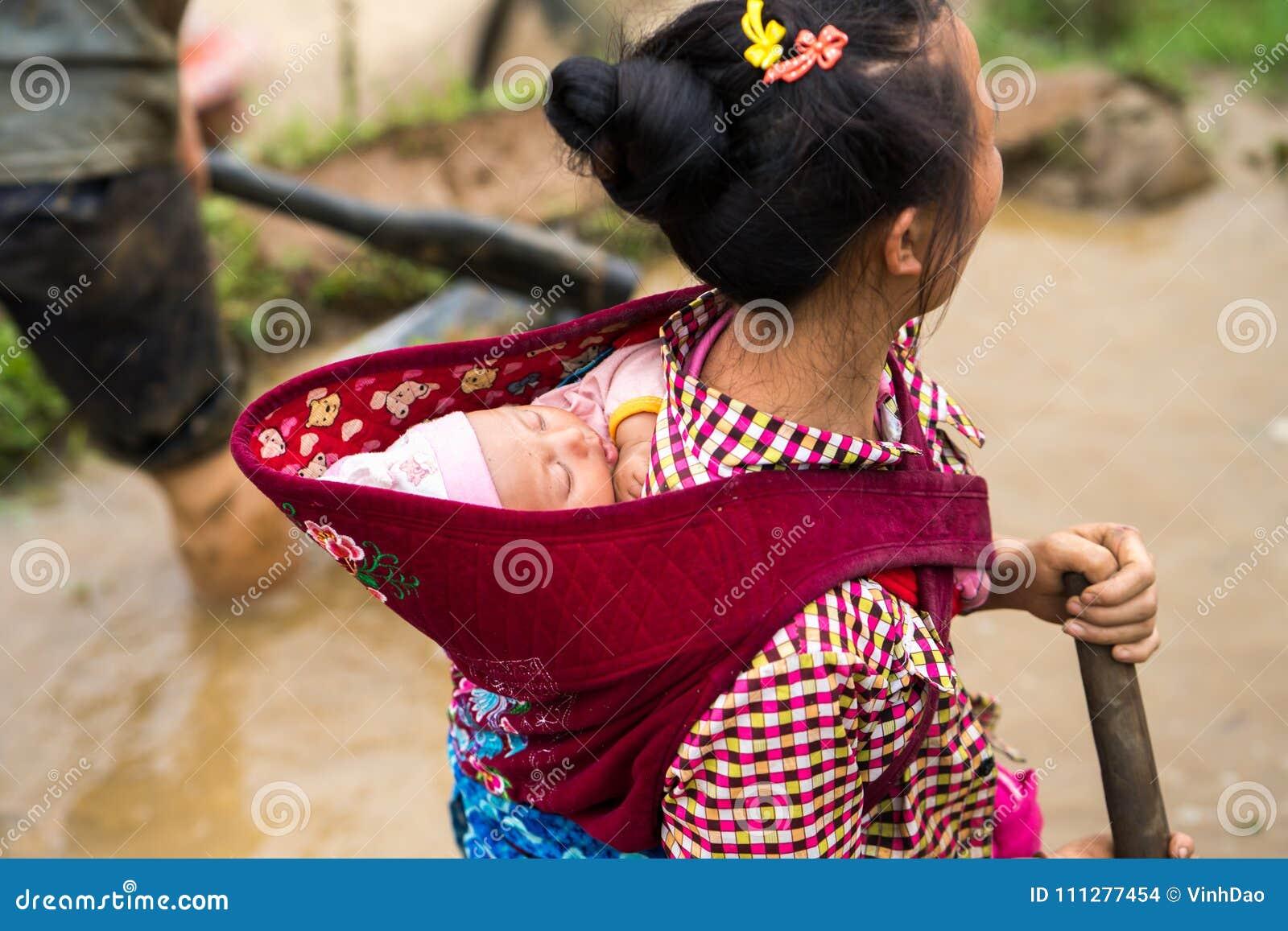 Y Ty Wietnam, Maj, - 12, 2017: Mniejszość etniczna matkuje z jej małym dzieckiem na tylnym działaniu na tarasowatym polu