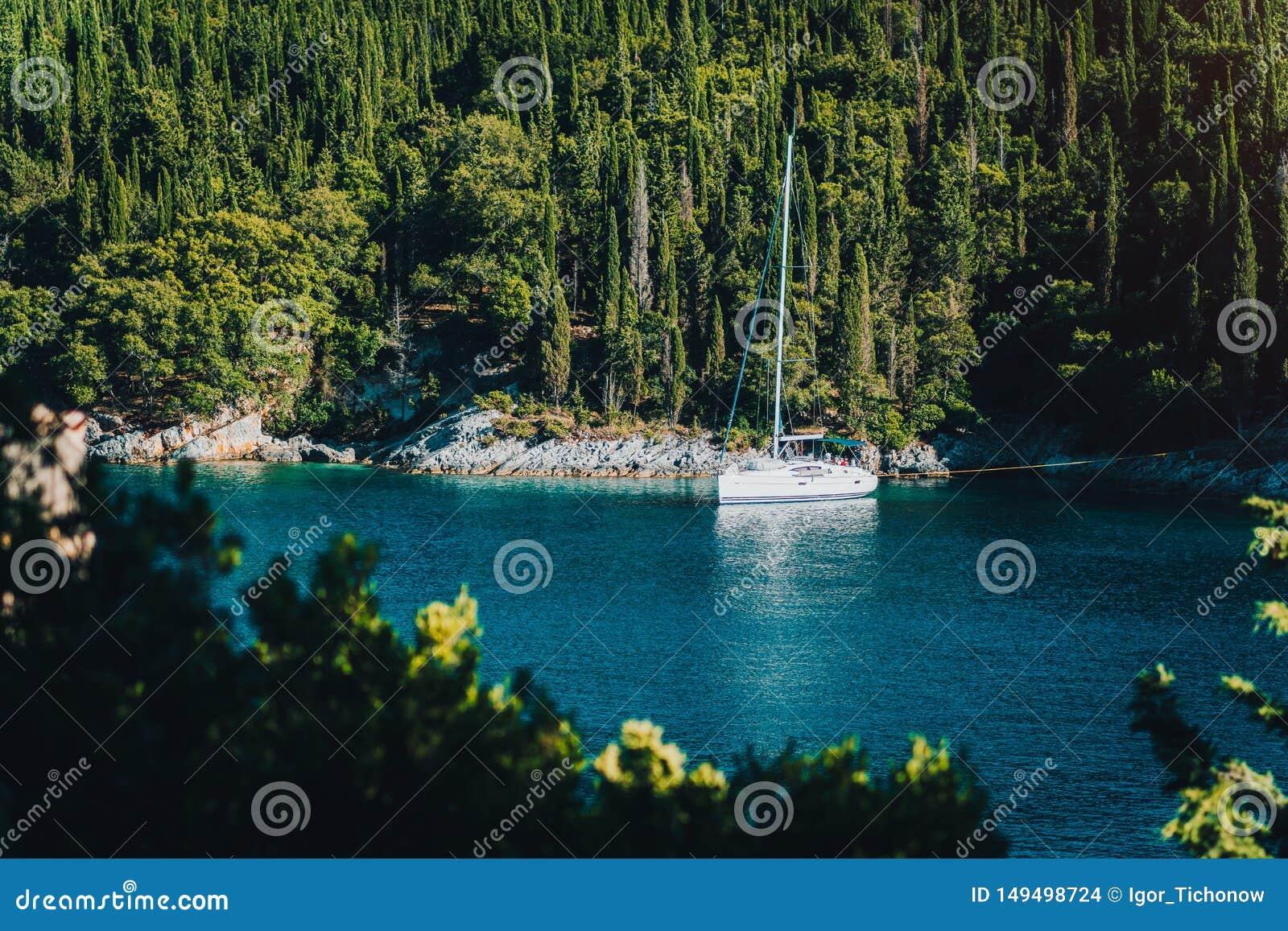 Yacht bianco della barca a vela attraccato nella baia della spiaggia di Foki con gli alberi di cipresso nel fondo, Fiskardo, Cefa