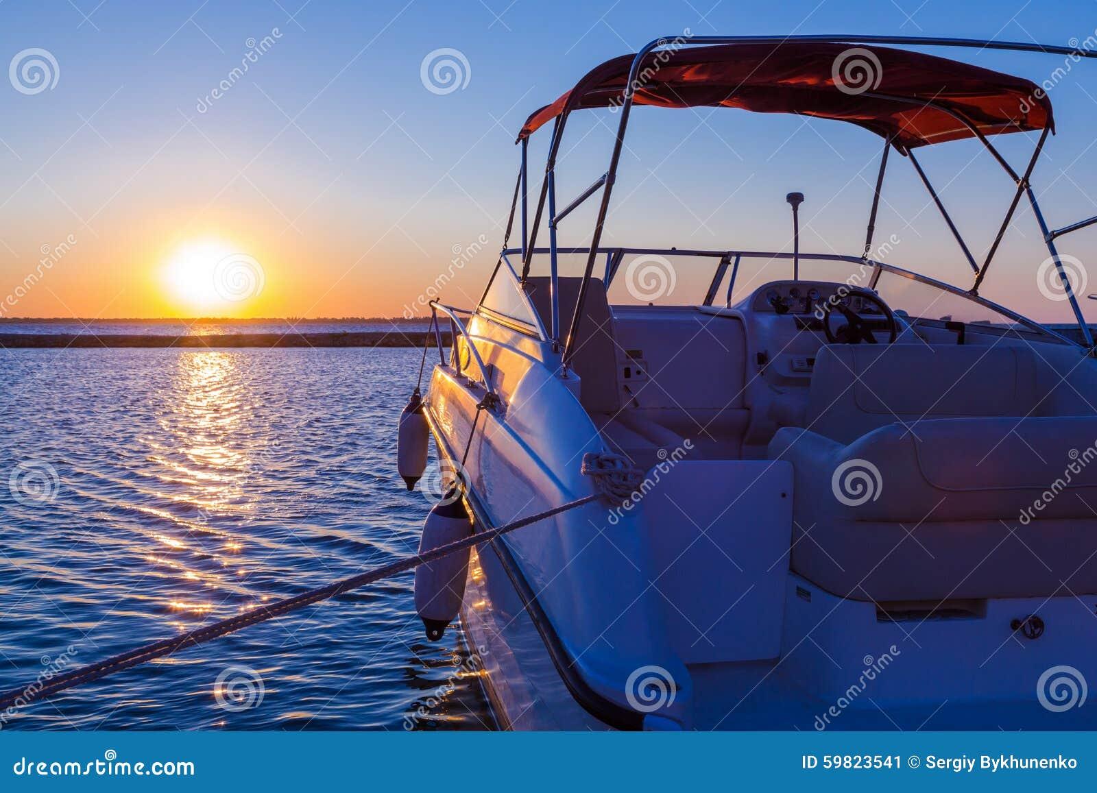 Yacht près du pilier contre le coucher du soleil