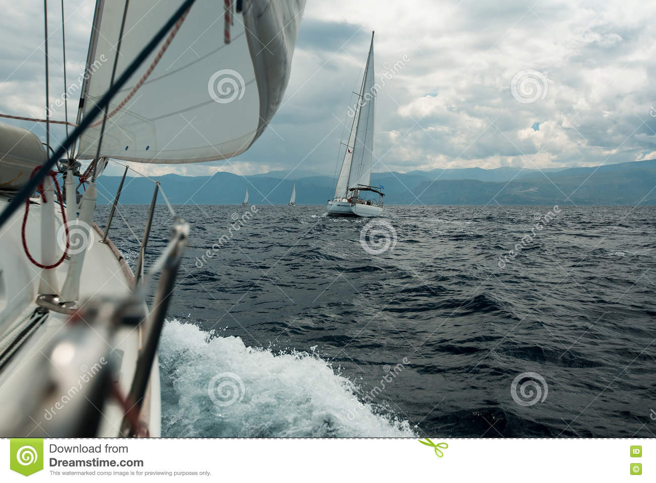 Yacht racing at sea in cloudy weather.