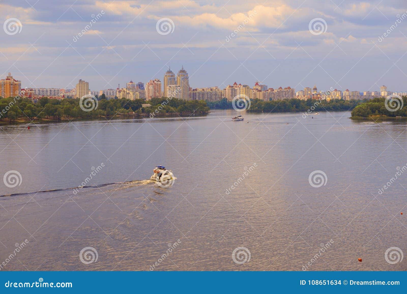 Yacht Schiff, Boot geht auf Oberfläche des Dnieper Dnipro, Dnepr-Fluss vor dem hintergrund der Stadtwolkenkratzer