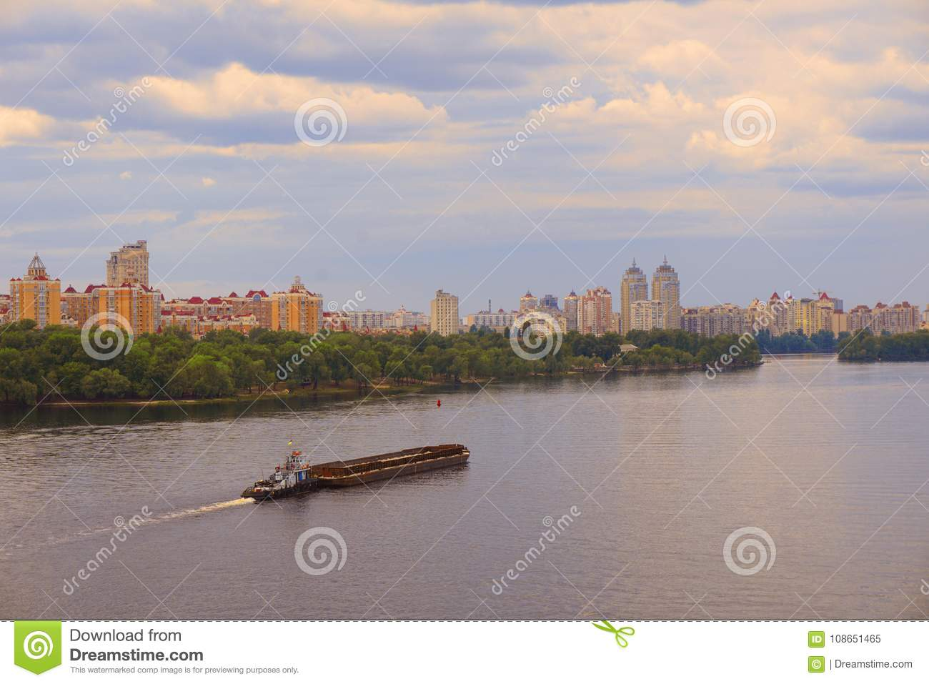 Yacht ship, boat goes on surface of the Dnieper Dnipro, Dnepr river against the background of city skyscrapers