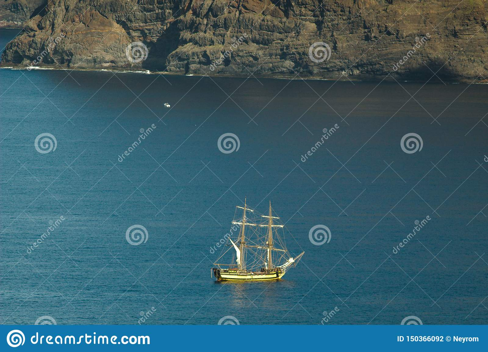 Yacht of tourists near the vertical cliffs Acantilados de Los Gigantes Cliffs of the Giants. View from Atlantic Ocean