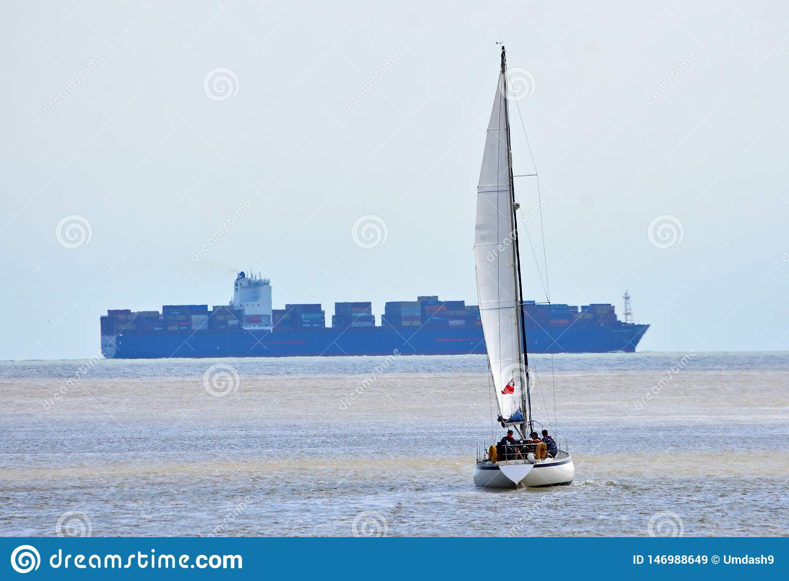 Yacht under Sail with large container ship in the background.