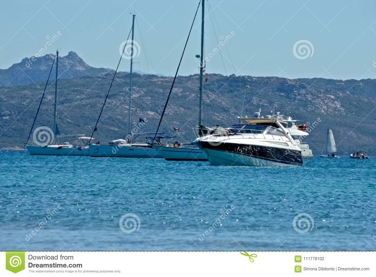 Yachts moored and sailing boats in a blue sea