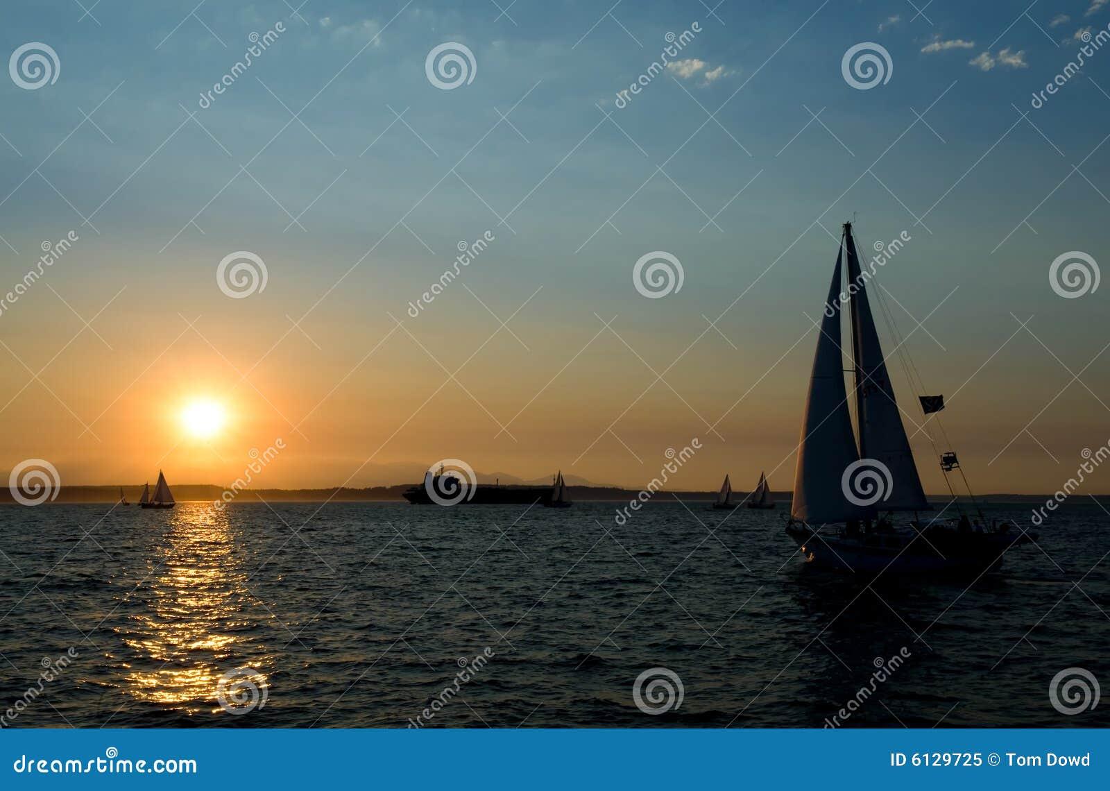 Yachts sailing at sunset
