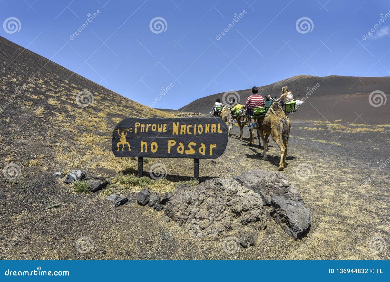 """YAIZA, ЛАНСАРОТЕ/ИСПАНИЯ - 12-ОЕ АПРЕЛЯ 2017: Туристы на верблюде входя в знак """"национальный парк национального парка Timanfaya о"""